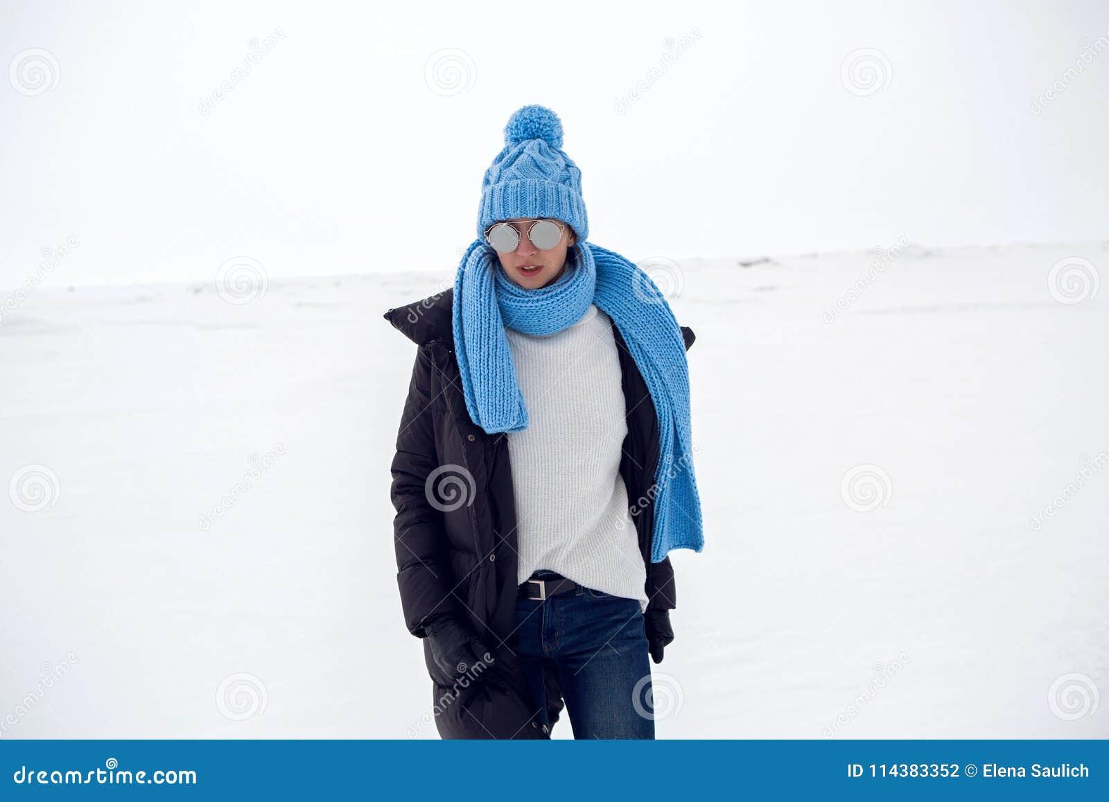 Mädchen, das in ein schneebedecktes Feld in einer Jacke läuft
