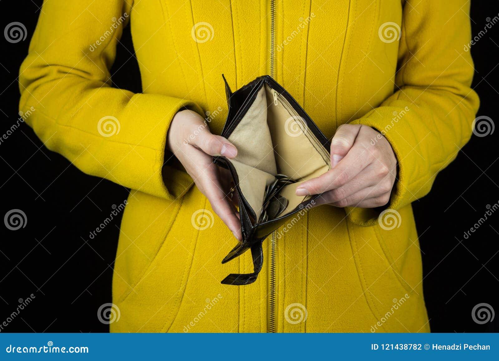 Mädchen, das einen leeren Geldbeutel auf einem schwarzen Hintergrund, Nahaufnahme hält
