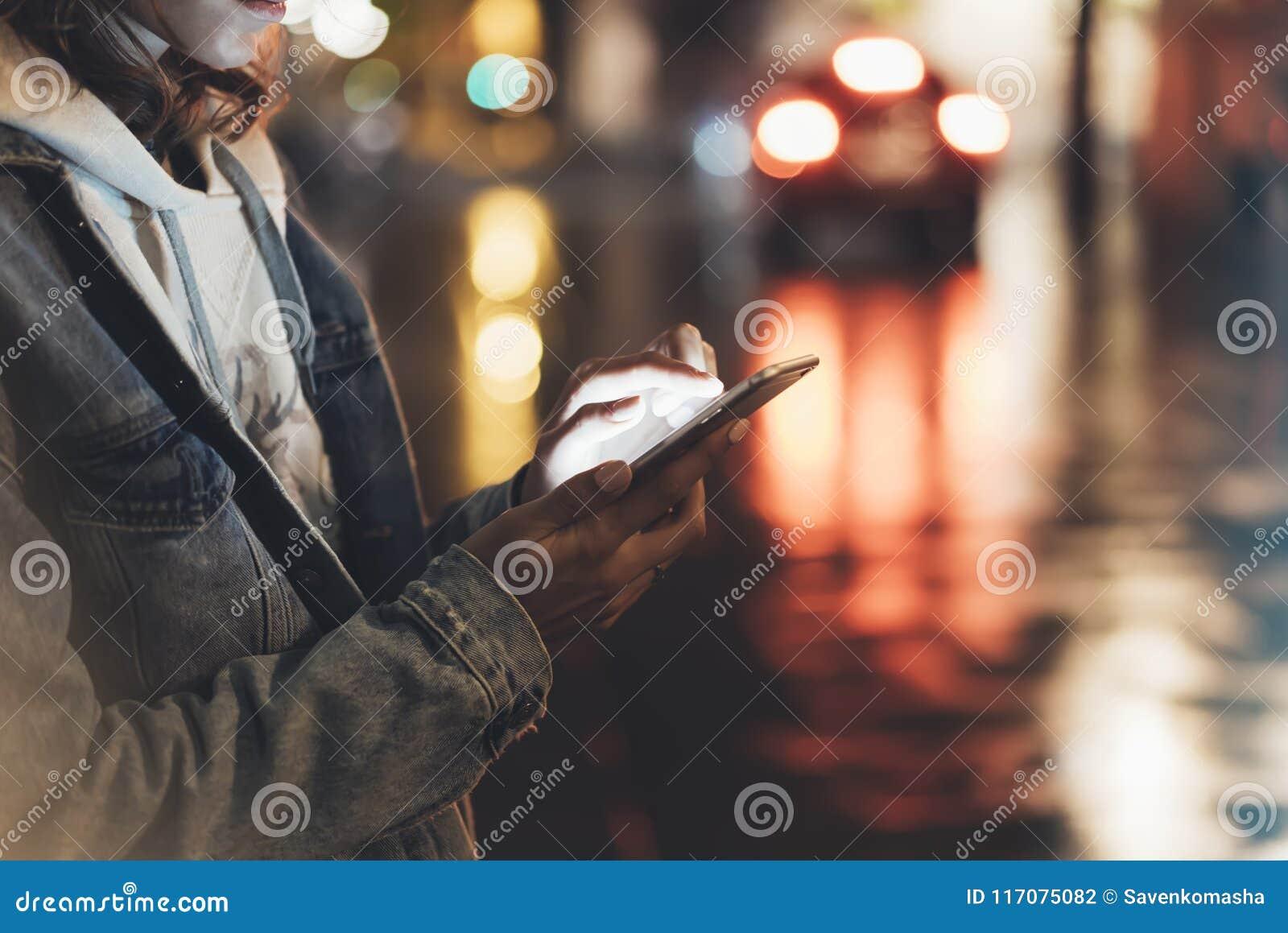Mädchen, das Finger auf Schirm Smartphone auf Hintergrundbeleuchtung bokeh Farblicht in der Nachtatmosphärischen Stadt, Hippie he