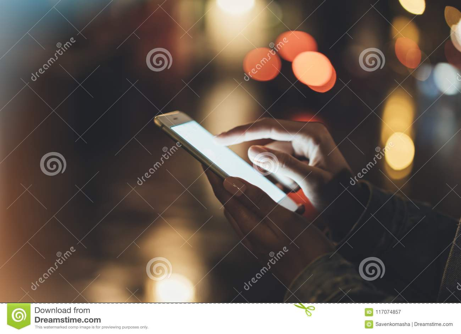 Mädchen, das Finger auf Schirm Smartphone auf Hintergrundbeleuchtungsglühen bokeh Licht Nachtin der atmosphärischen Weihnachtssta