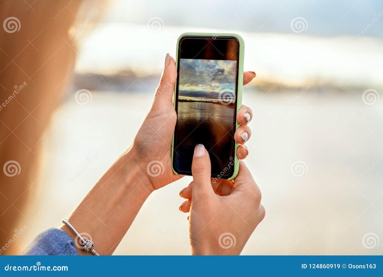 Mädchen, das Fotos einer Landschaft, Nahaufnahme eines Telefons in ihr macht