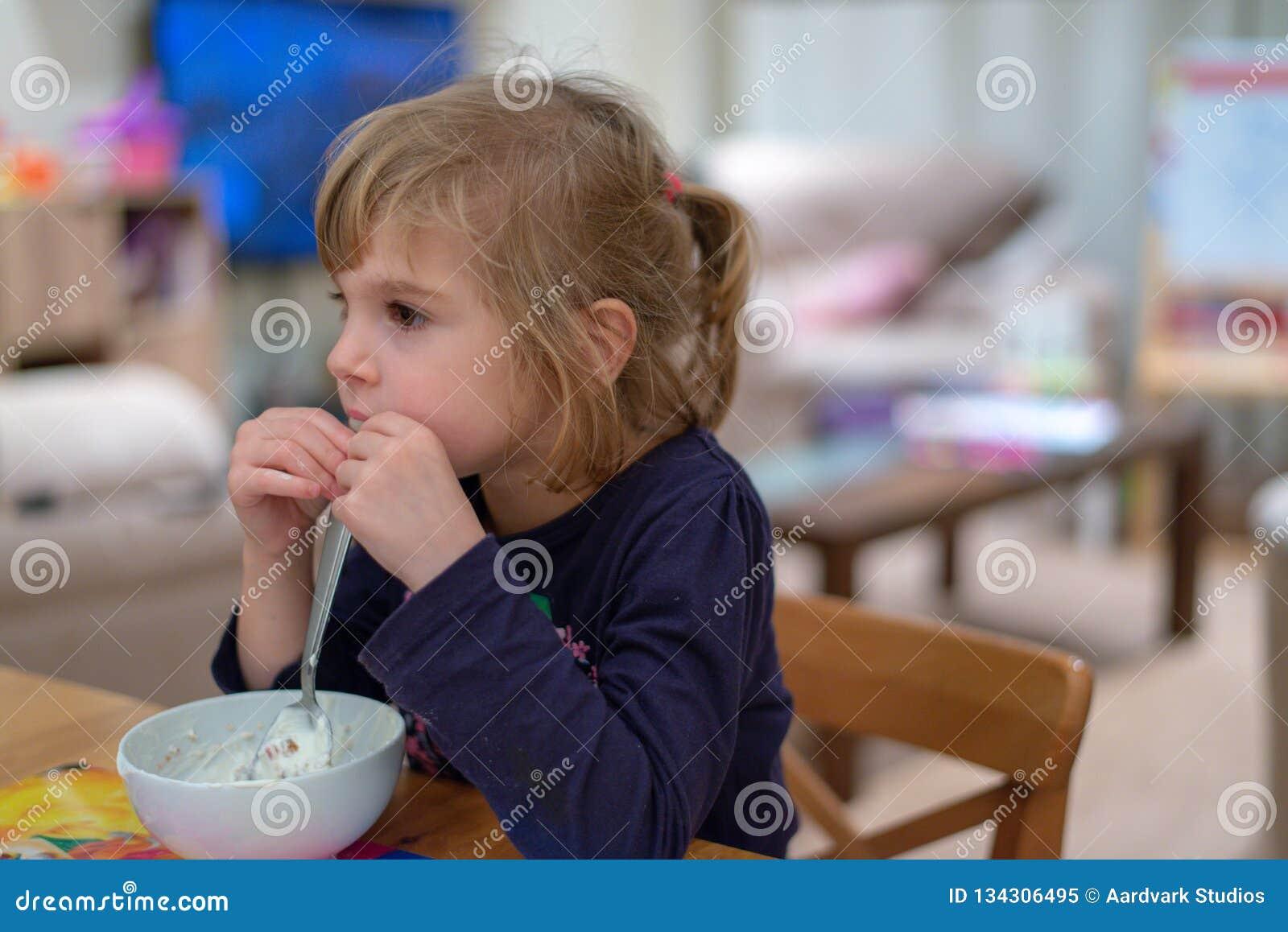 Mädchen, das an Frühstücksessen muesli mit Jogurt von der weißen Schüssel sitzt