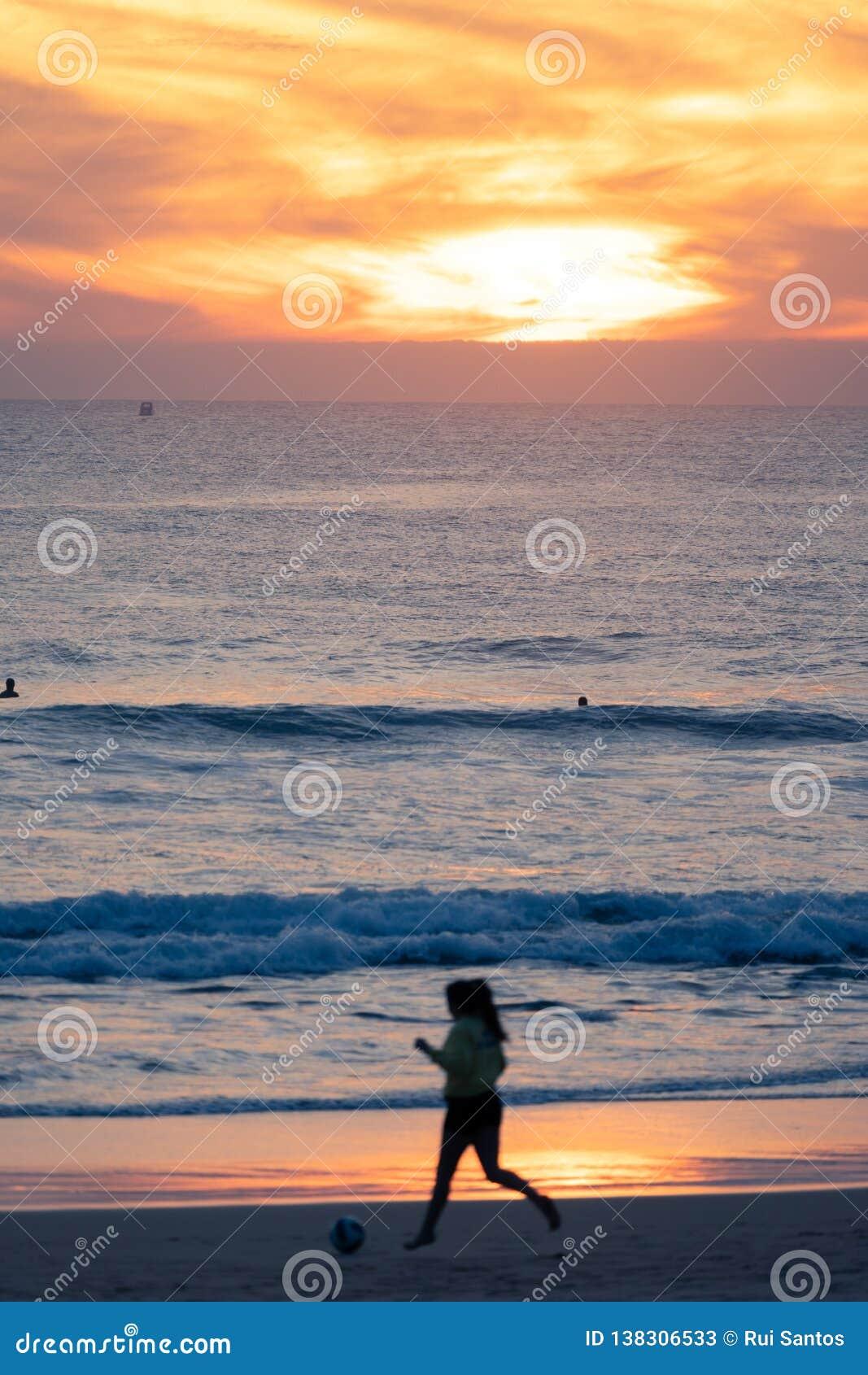 Mädchen, das Fußball bei Sonnenuntergang, Carcavelos-Strand, Lissabon, Portugal spielt