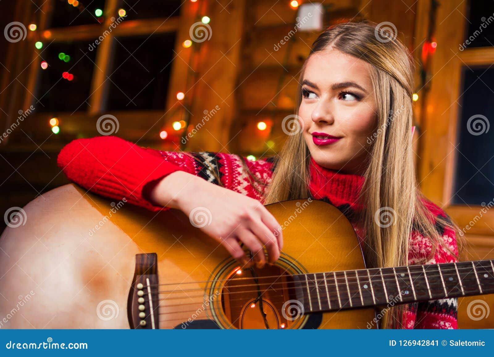 Mädchen, das Gitarre in einem Blockhaus spielt