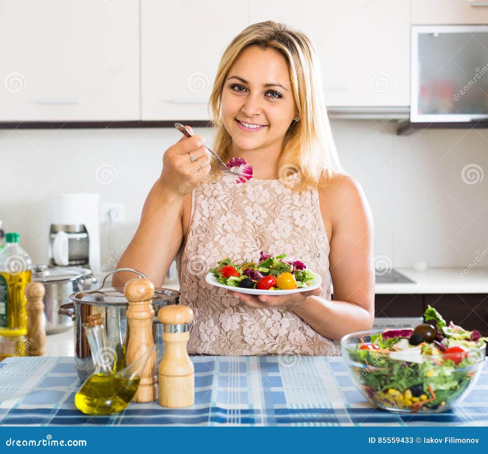 Mädchen, das am Küchentisch mit Platte des Salats steht