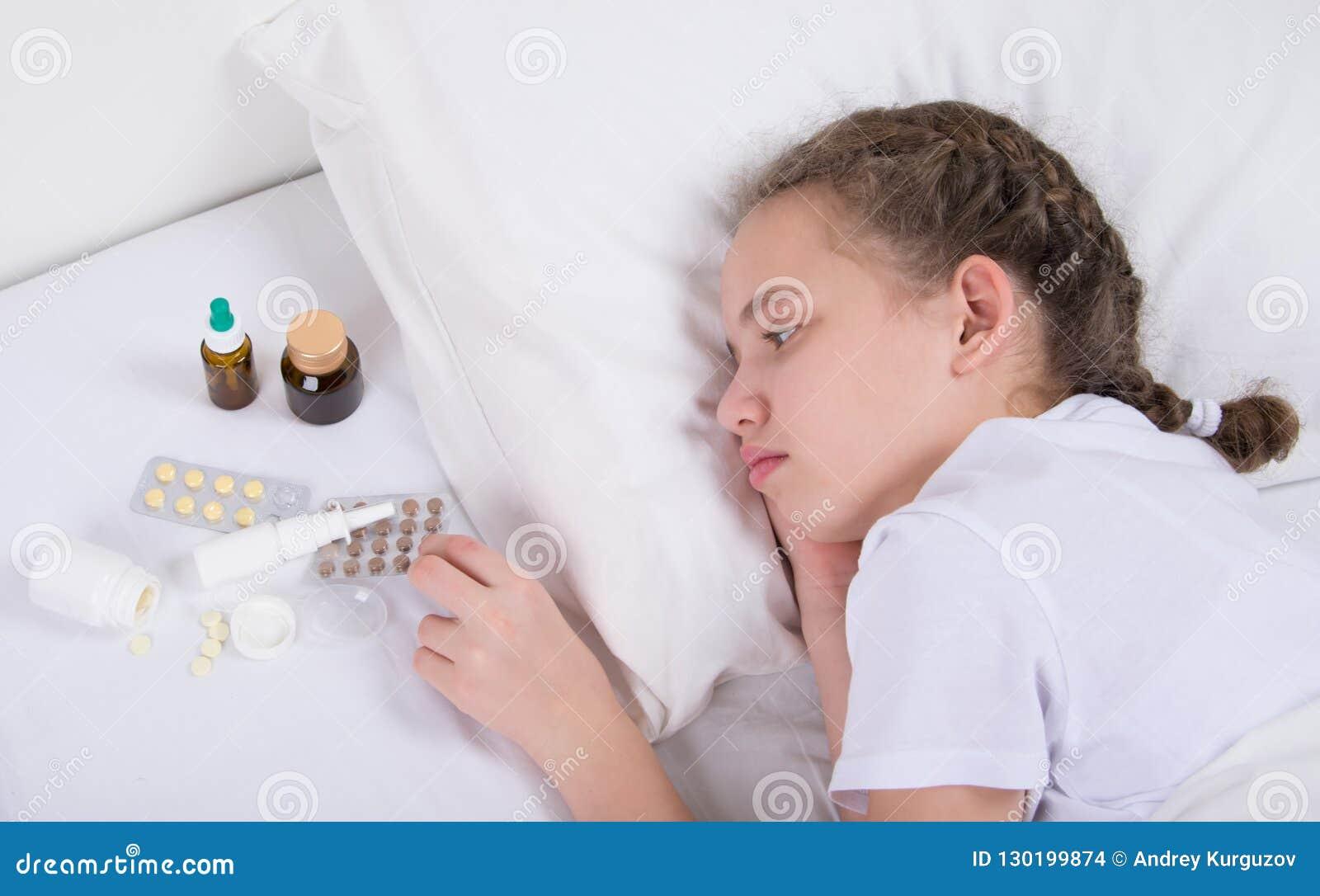 Mädchen, das krank ist und im Bett, nahe einem Satz Pillen und mextures liegt