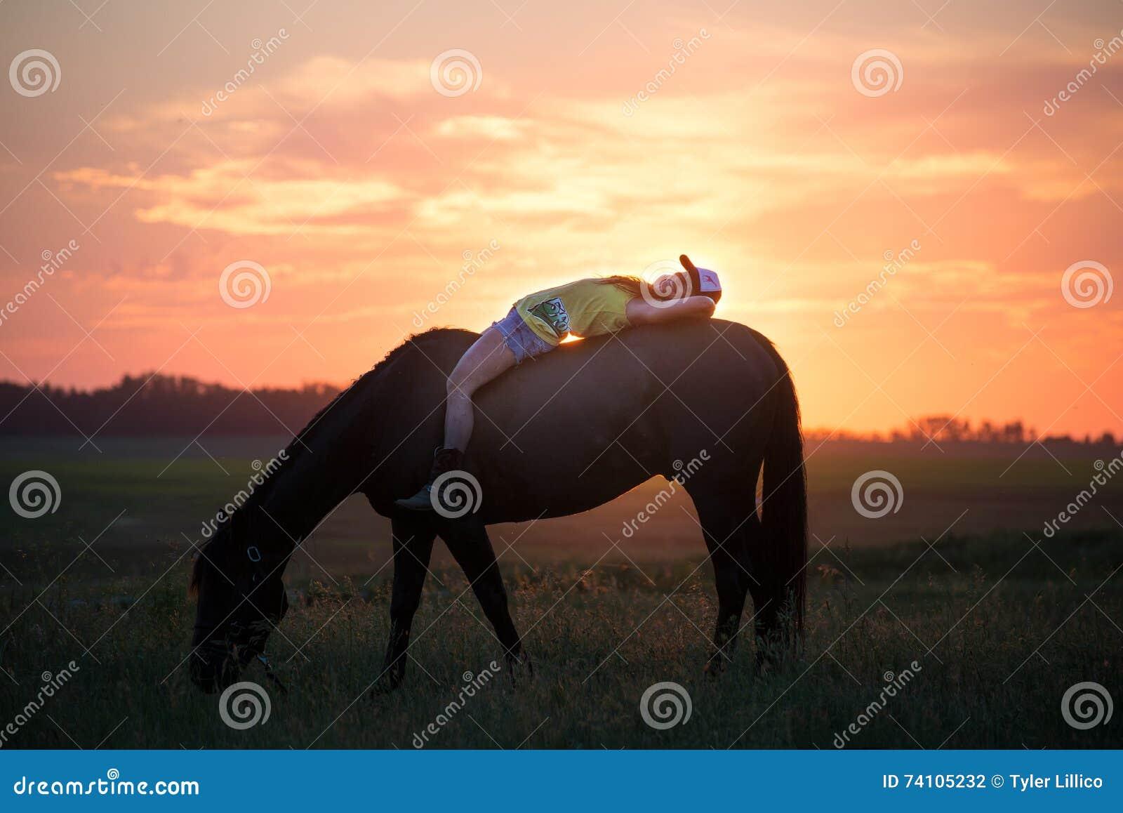mädchen das ohne sattel auf ihrem pferd liegt stockfoto