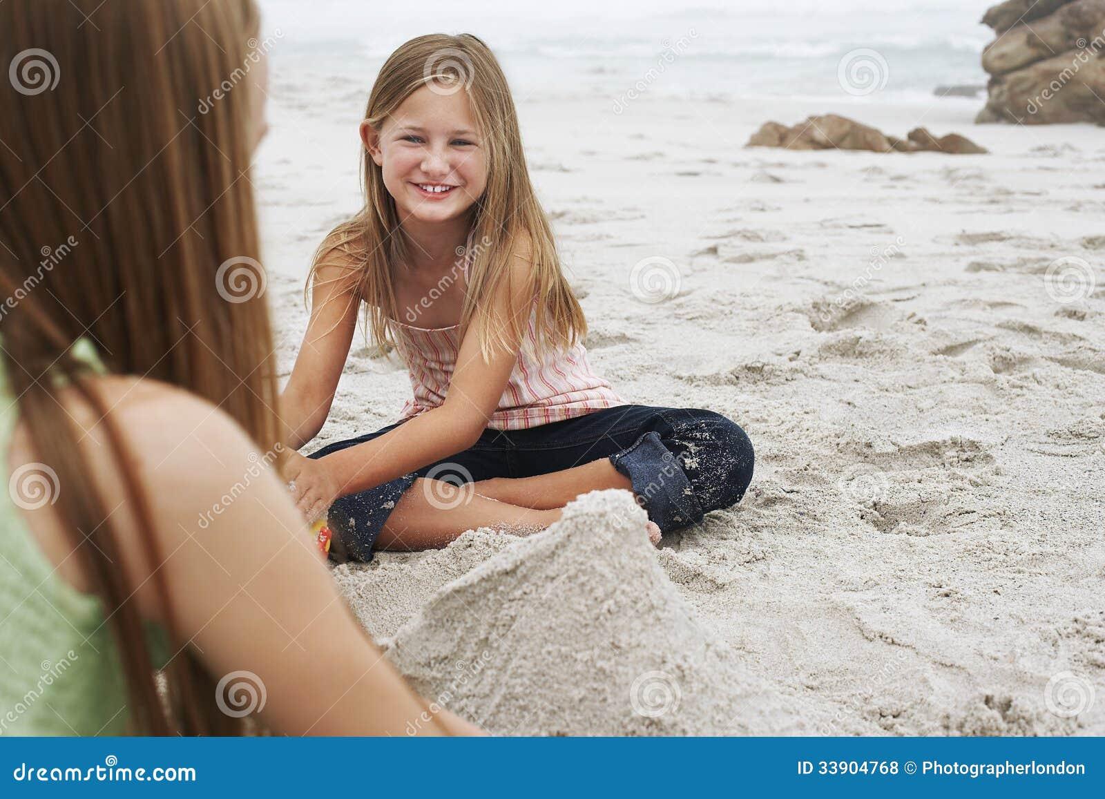 Mädchen, das Sandburg mit Schwester At Beach macht
