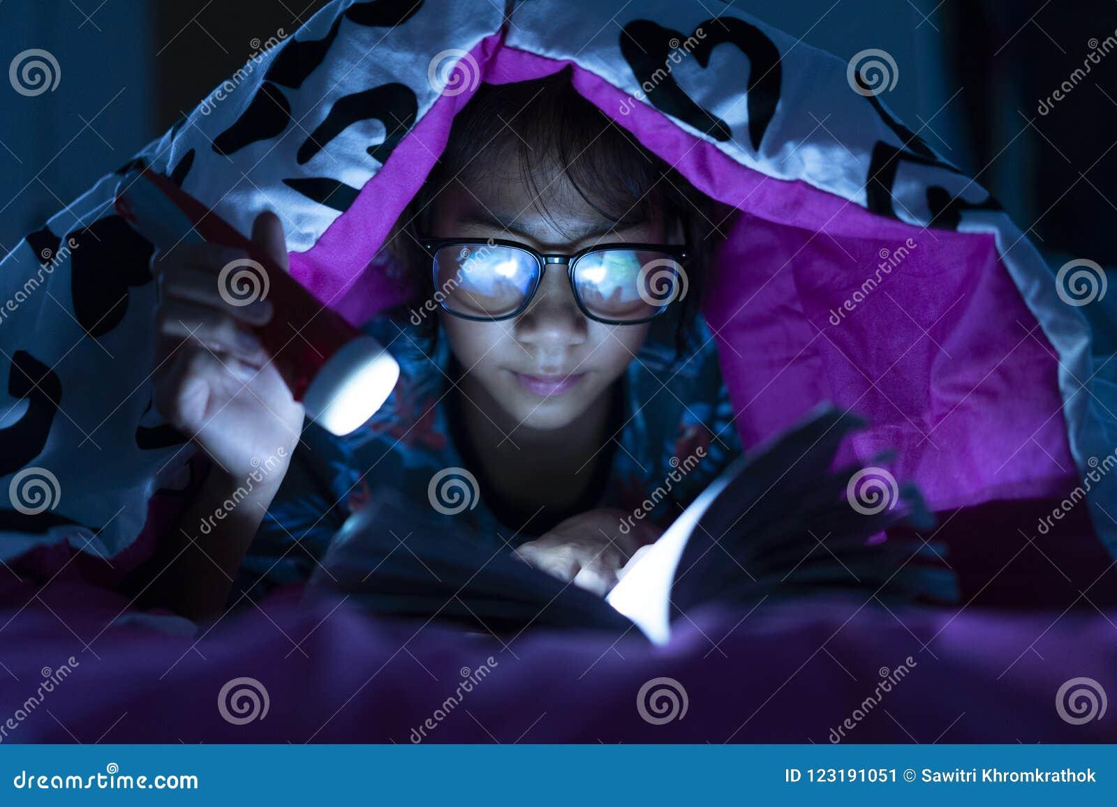 Mädchen, das Taschenlampe während Abnutzungsglas-Lesebuchdecke im Bettraum hält