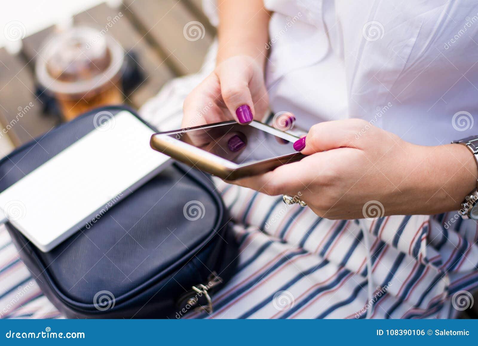 Mädchen, das Telefon bei der Aufladung auf der Energiebank verwendet