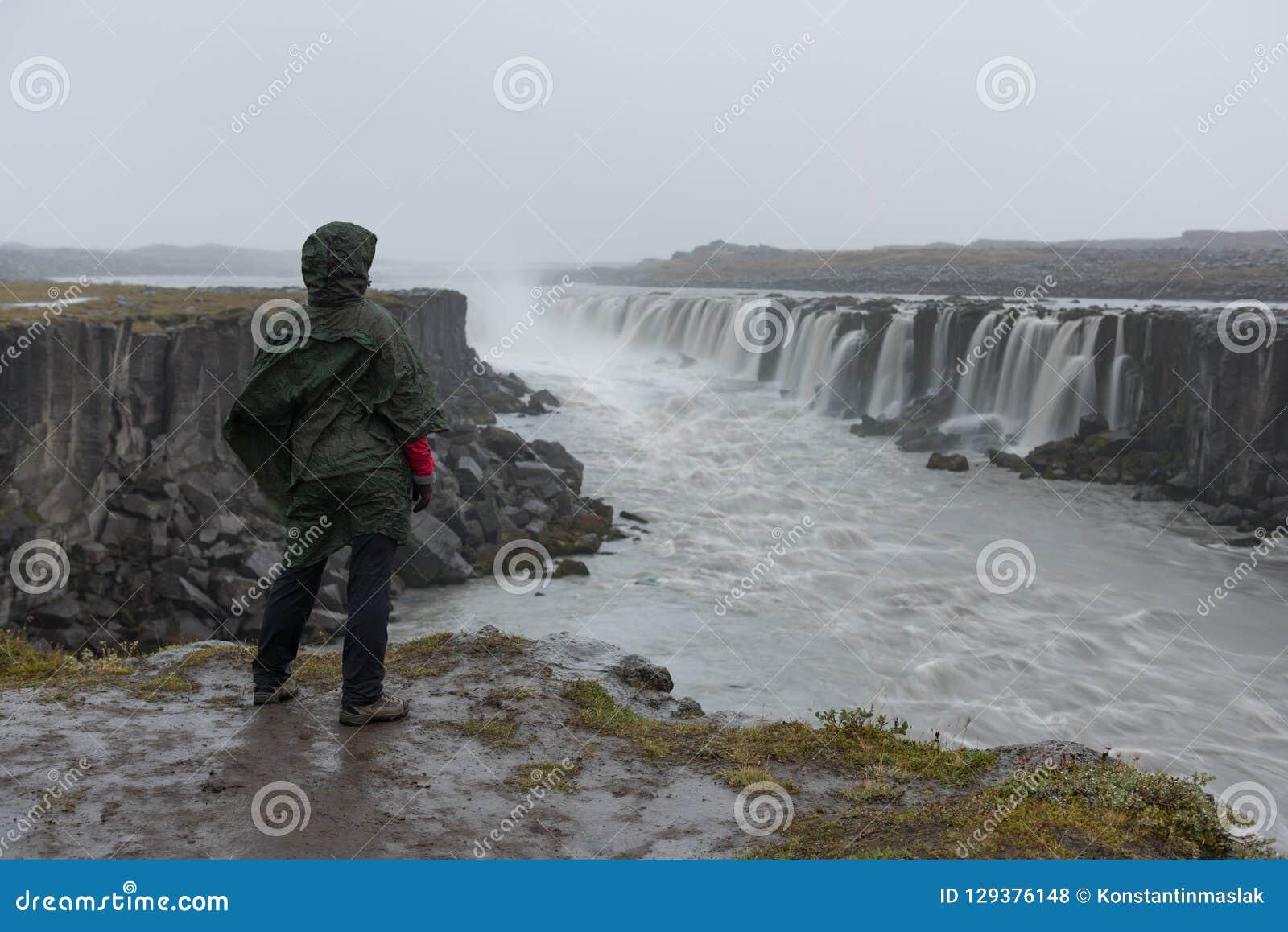 Mädchen in den wasserdichten Jackenständen auf der Klippe auf Hintergrund des Wasserfalls in Island
