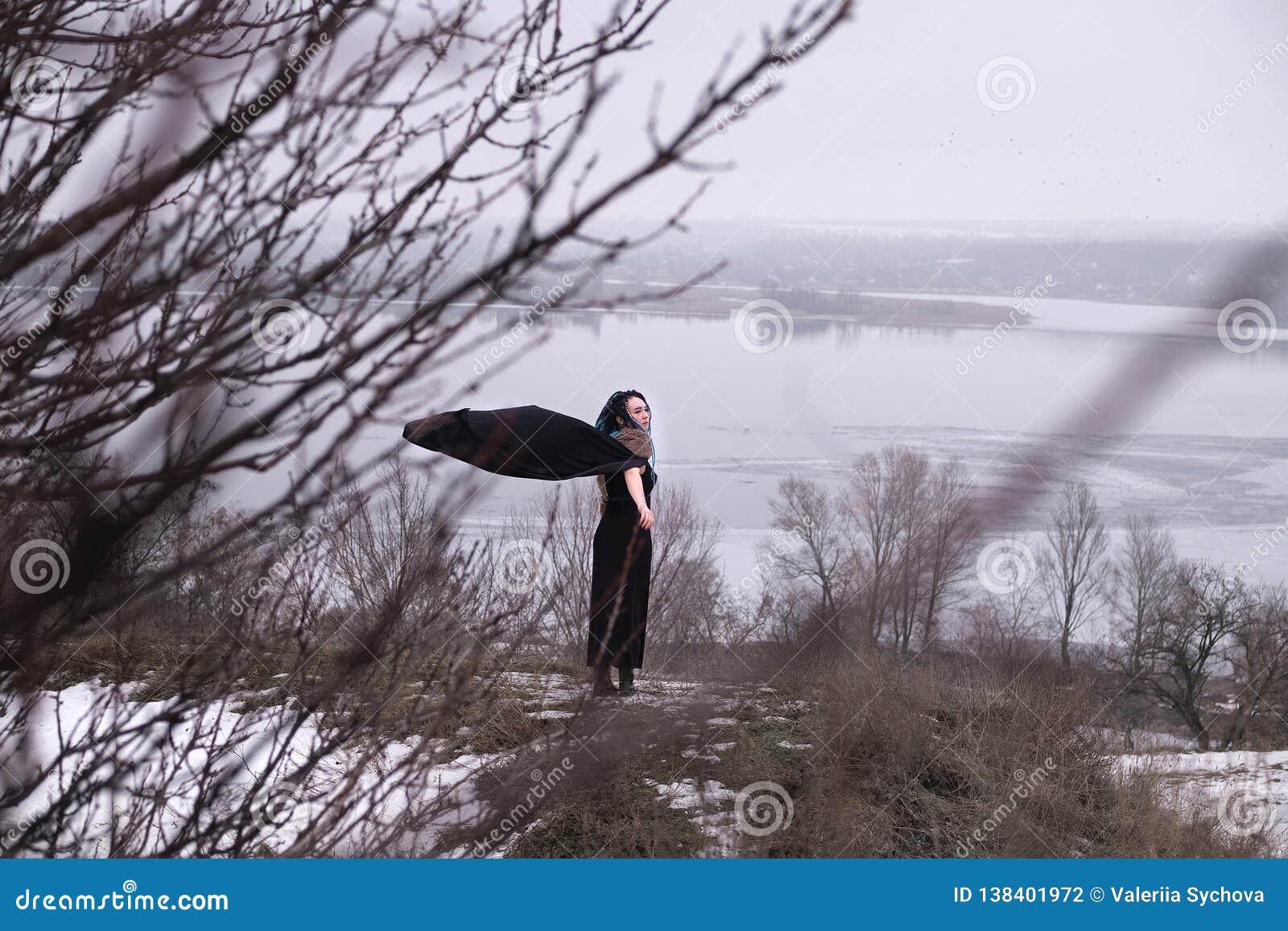Mädchen in der schwarzen Kleiderstellung auf der Straße zwischen den Büschen und den Bäumen Viking-Frau mit einer Klinge in einem