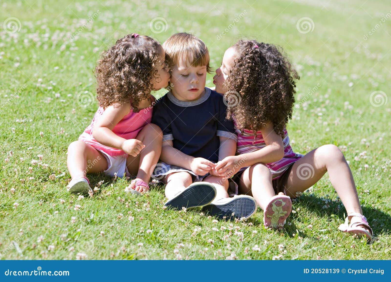 Zwei entzückende kleine mädchen die einen netten kleinen jungen