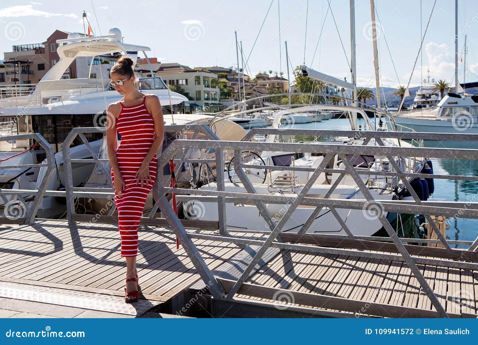 Mädchen in einem roten gestreiften Kleid steht an der Yacht