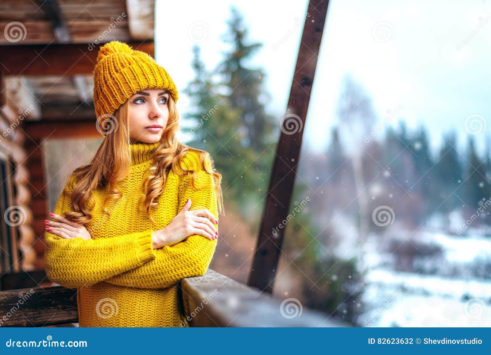 Mädchen in einem Strickpulli, der Schnee betrachtet