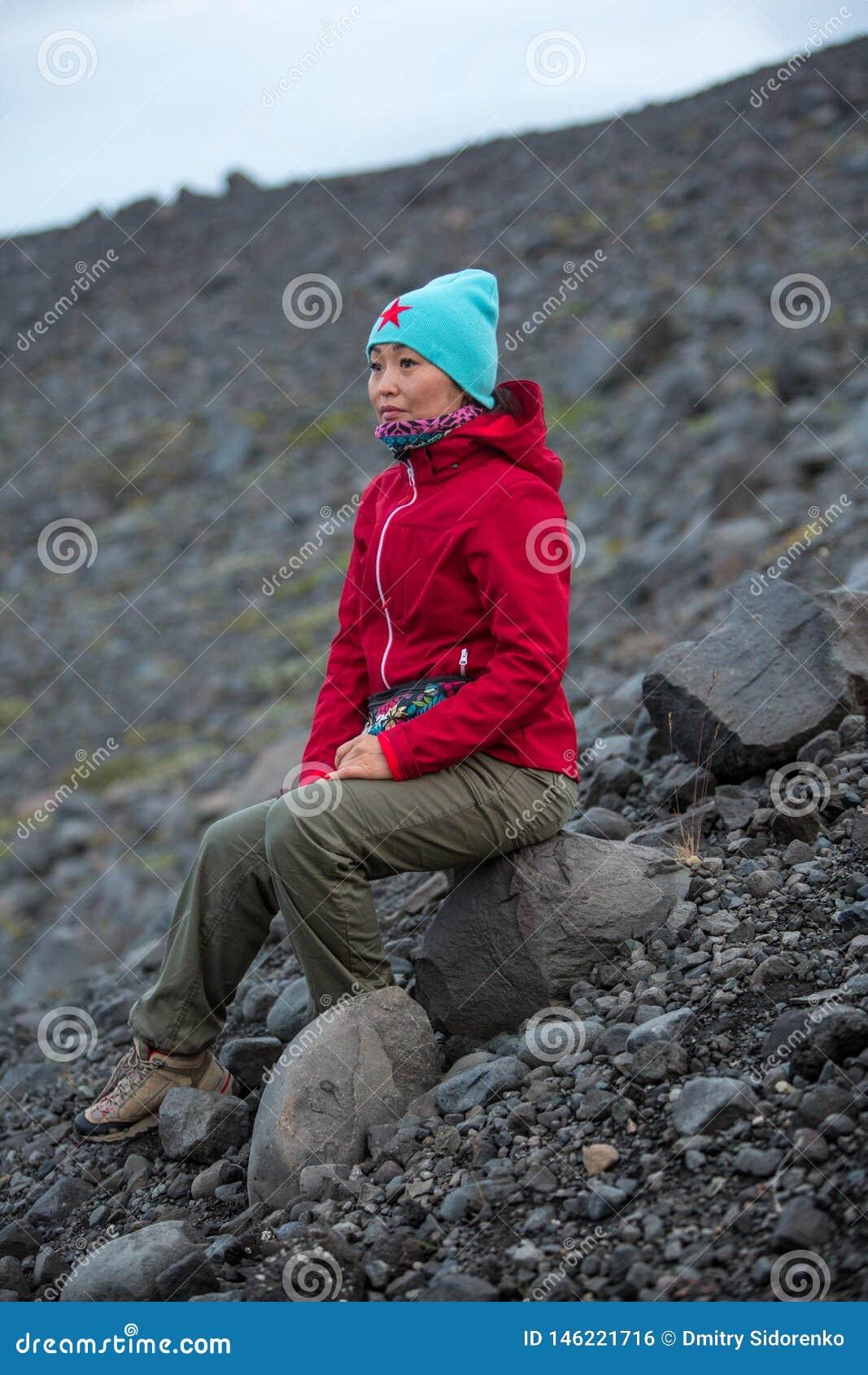 Mädchen in einer roten Jacke, die auf einem Stein auf dem Hintergrund einer felsigen Steigung sitzt