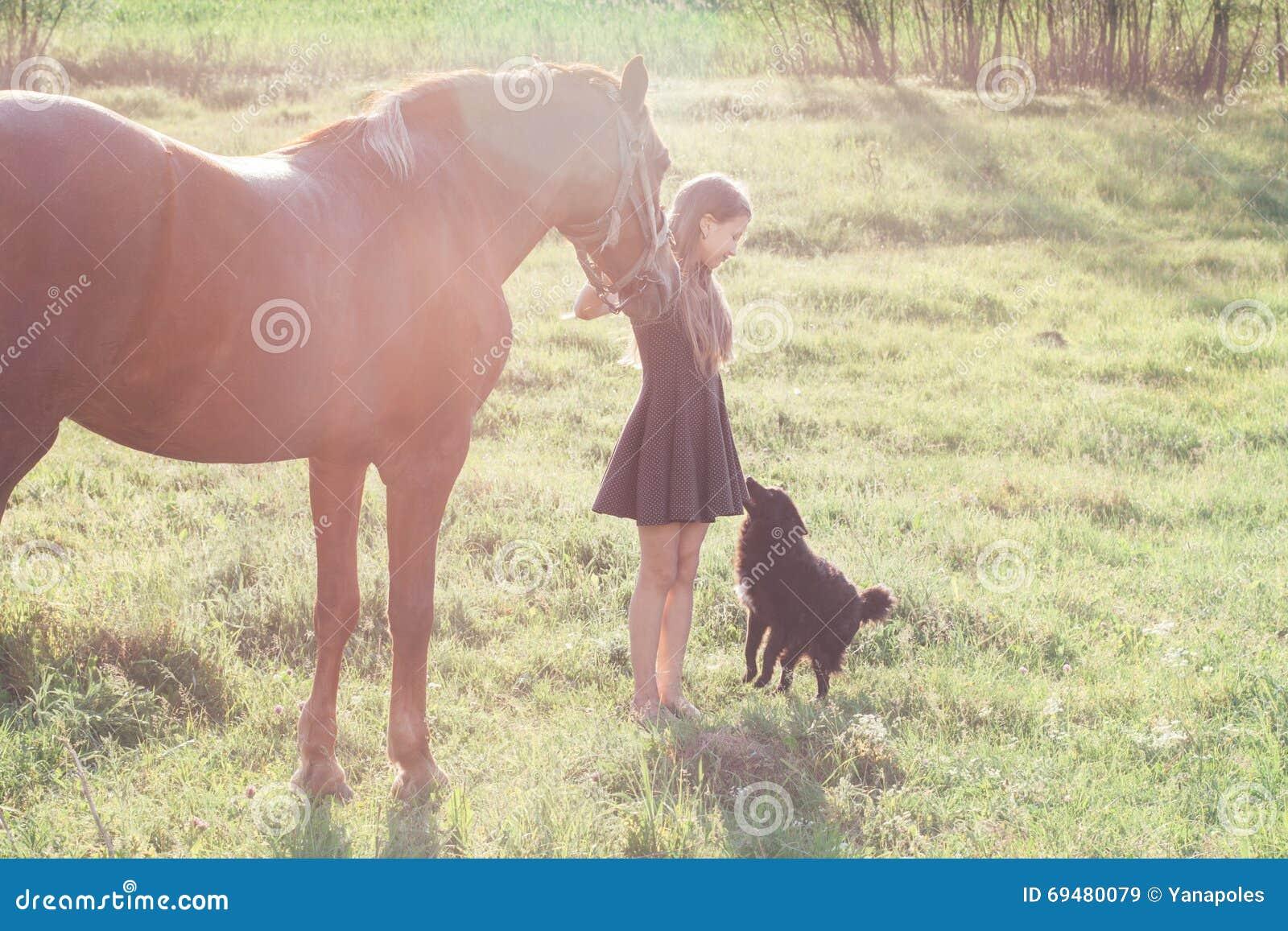 Mädchen führt ihr Pferd und das Streichen des schwarzen Hundes