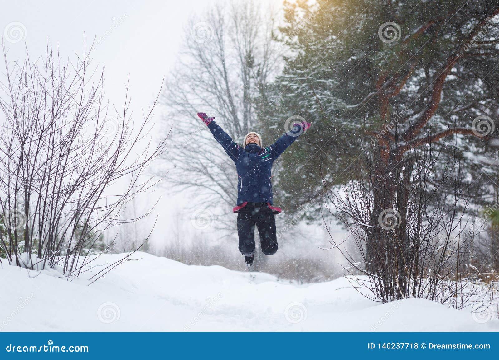 Mädchen freut sich im Winter, ein Mädchen, das in den Winterwald springt