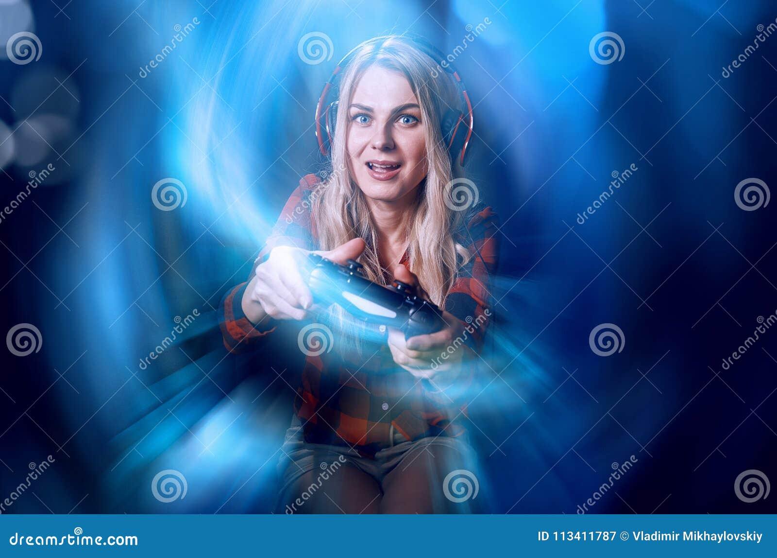 Mädchen Gamer in den Kopfhörern und mit einem Steuerknüppel, der enthusiastisch auf der Konsole spielt