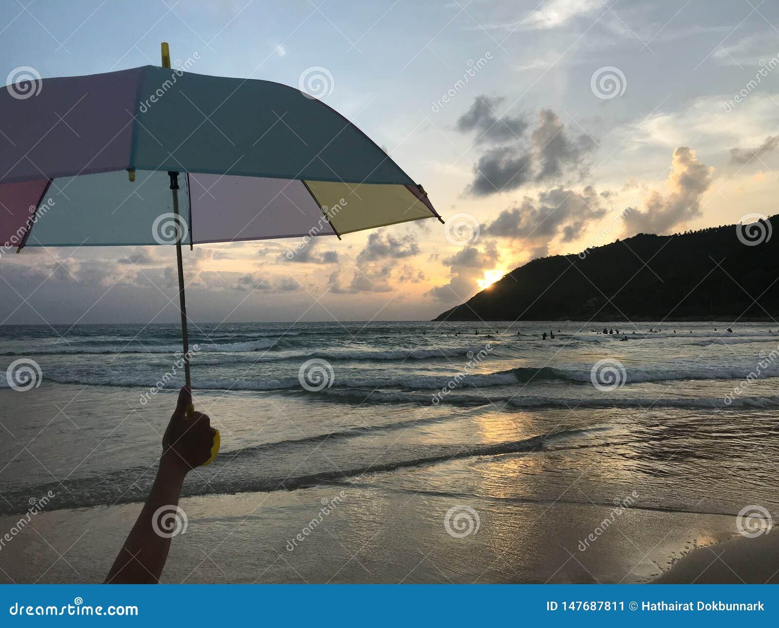 Mädchen hält einen bunten Pastellregenschirm auf dem Strand mit überraschendem Sonnenuntergang