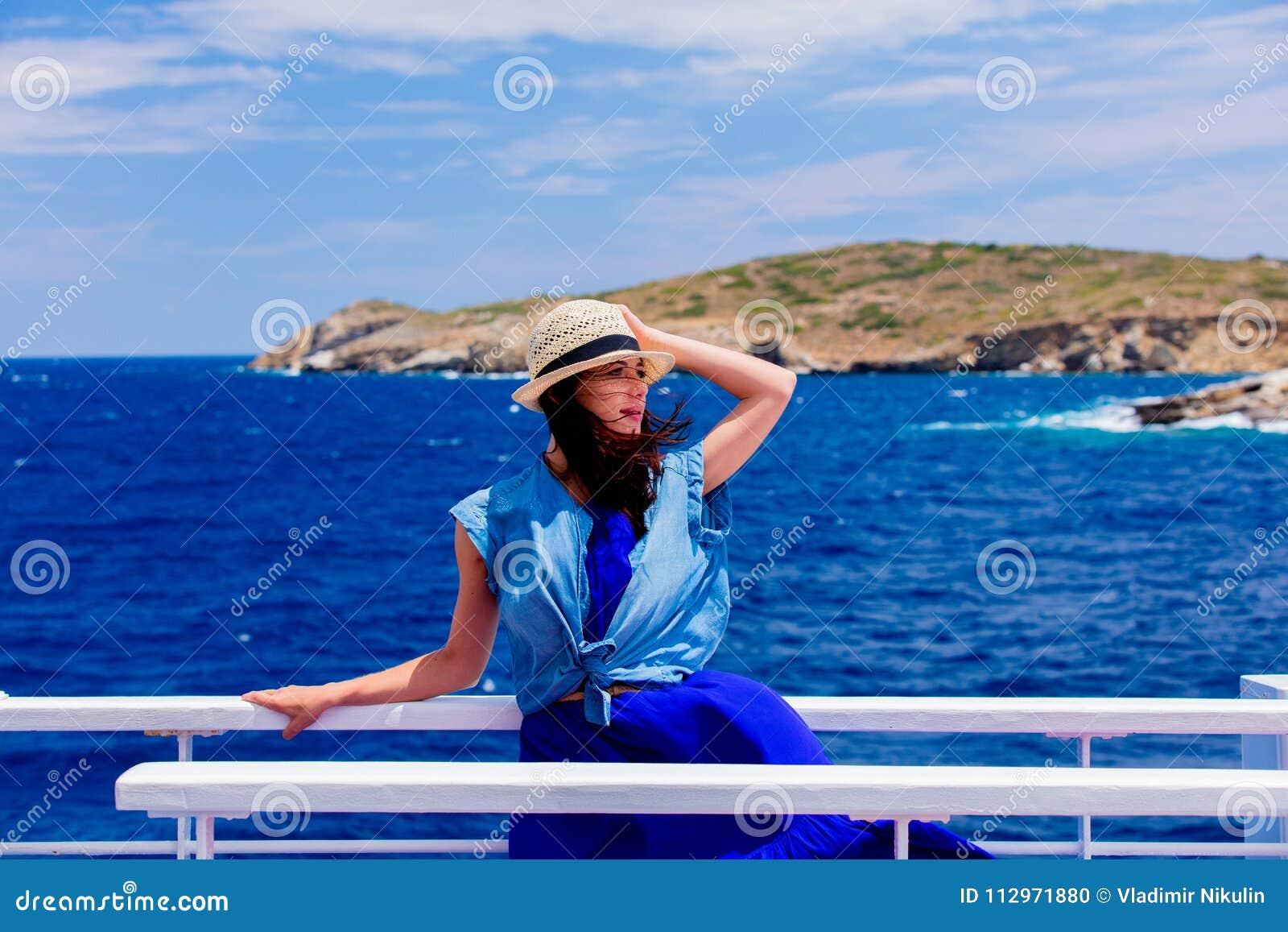 Mädchen im blauen Kleid und Hut haben eine Reise auf einem Boot