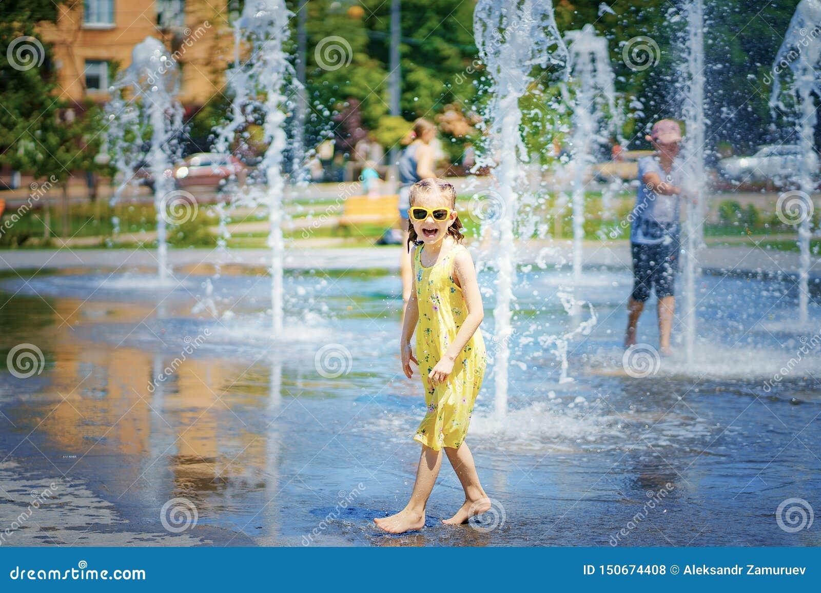 Mädchen im gelben Kleid, das Spaß den Spray des Brunnens genießend spielt und hat