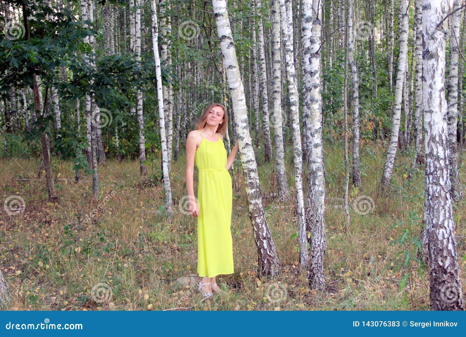 Mädchen im hellen gelben Kleid am Abend im Birkenwald