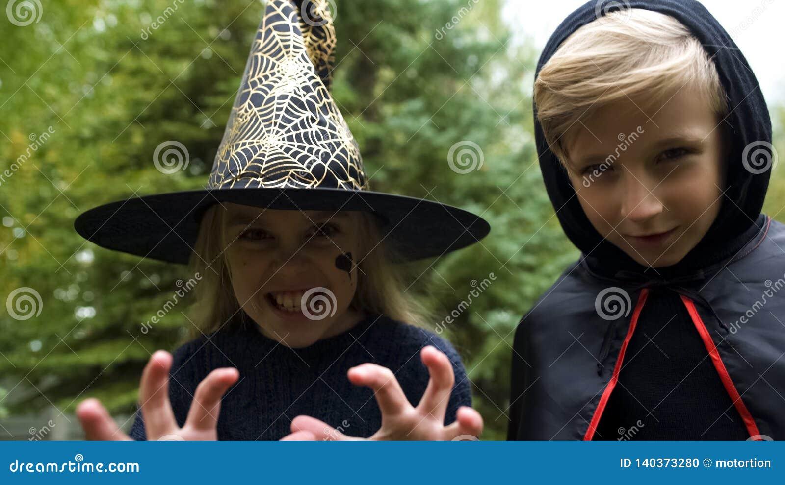 Mädchen im Hexenhut und -jungen im Umhang, der Kamera, Knurren gespenstisch, Halloween jagt