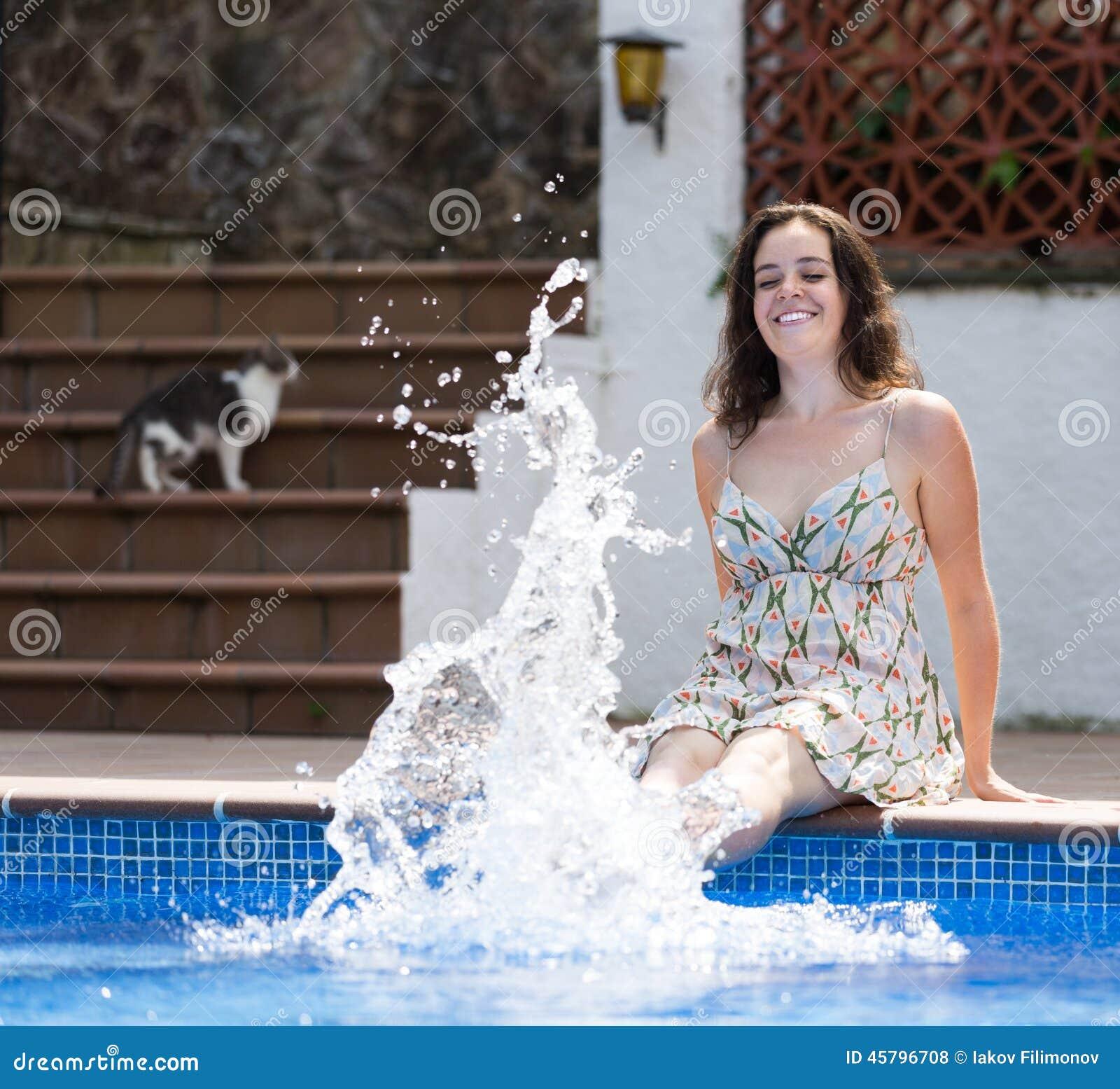 Mädchen im Kleid, das nahe Pool stillsteht