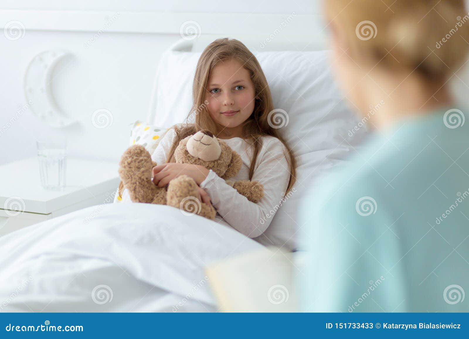Mädchen im Krankenhaus, das einen Teddybären hält