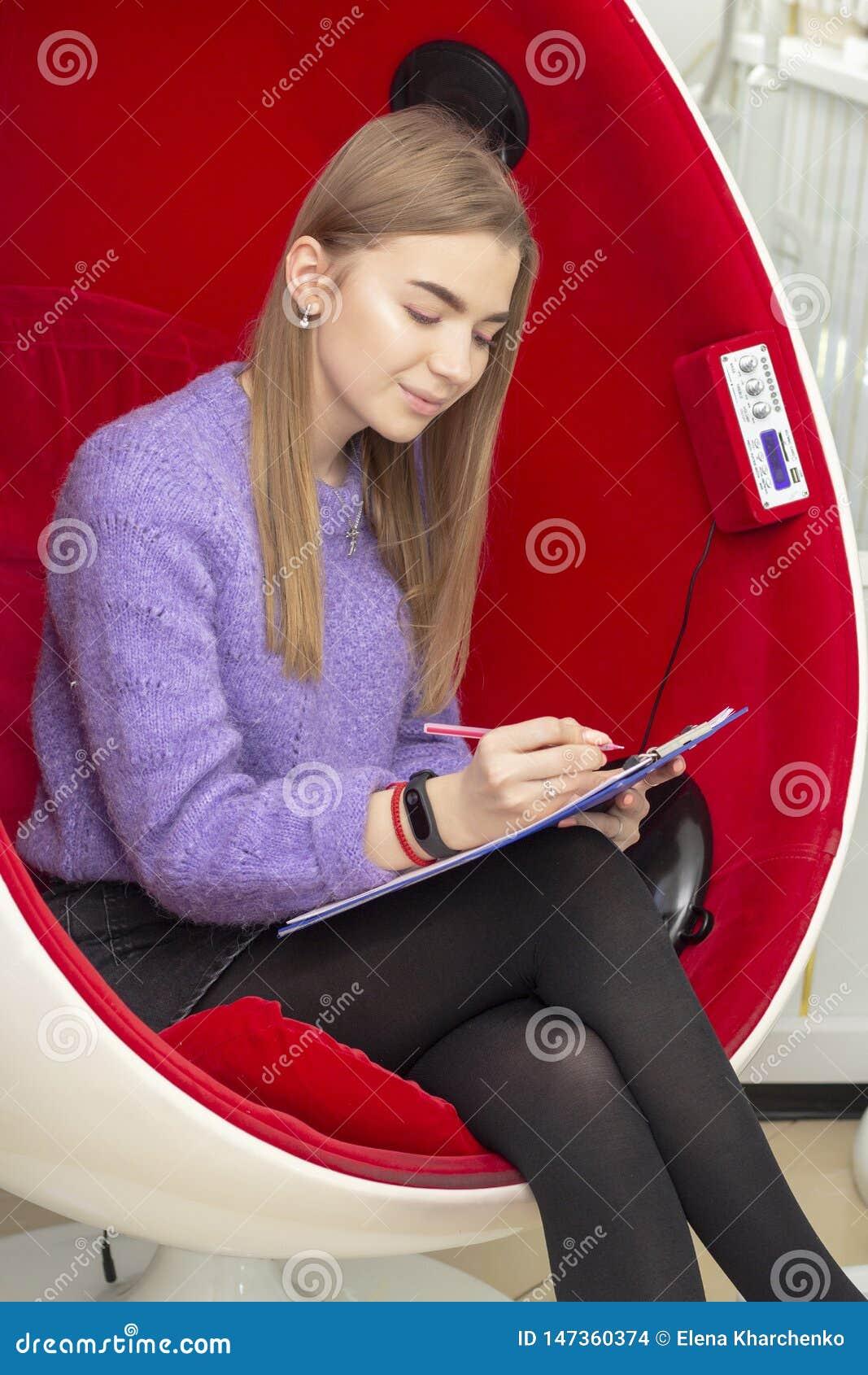 Mädchen im Schönheitswohnzimmer liest und unterzeichnet einen Wartungsvertrag