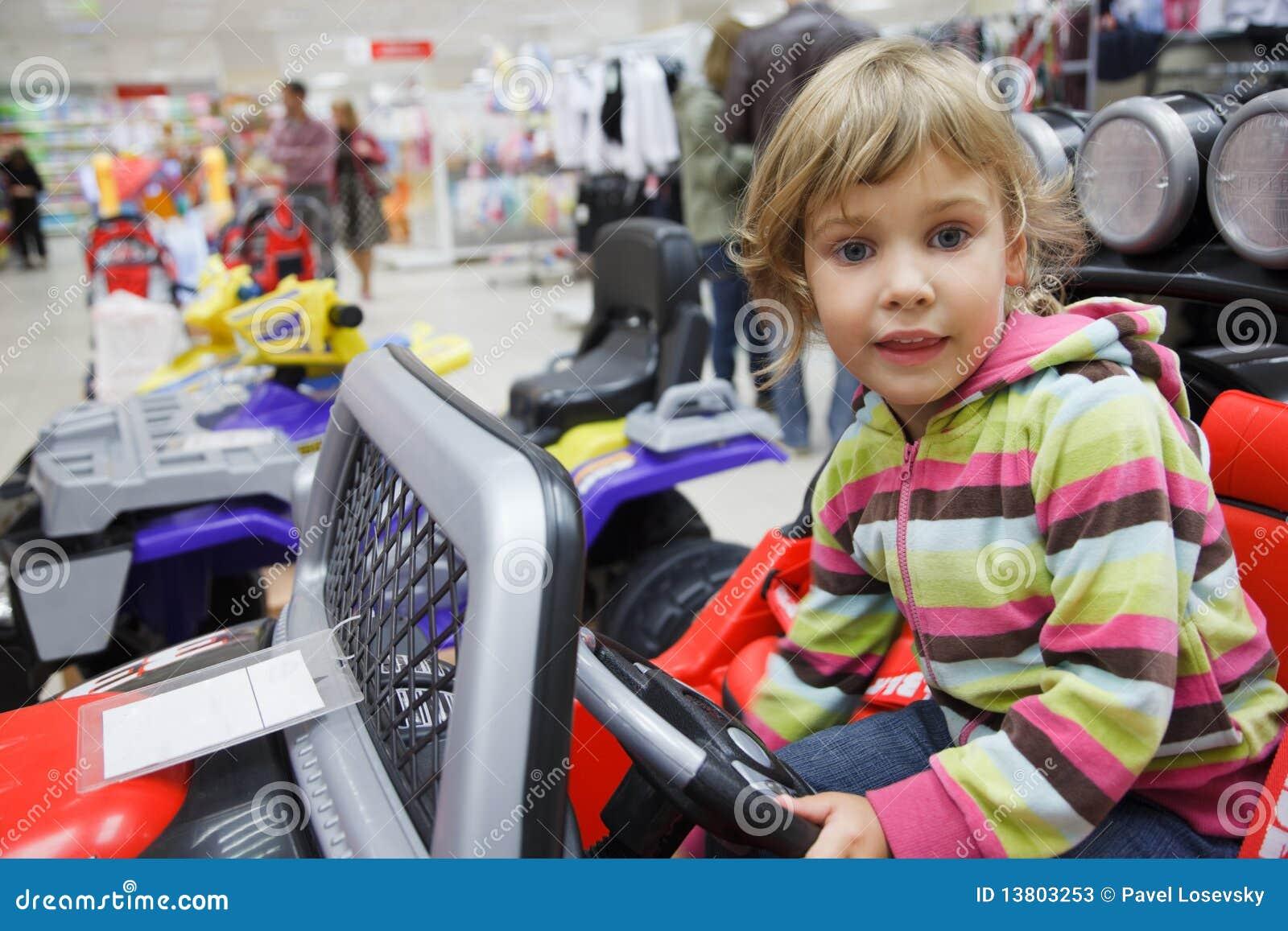 Mädchen im Supermarkt alleine in der Abteilung der Spielwaren