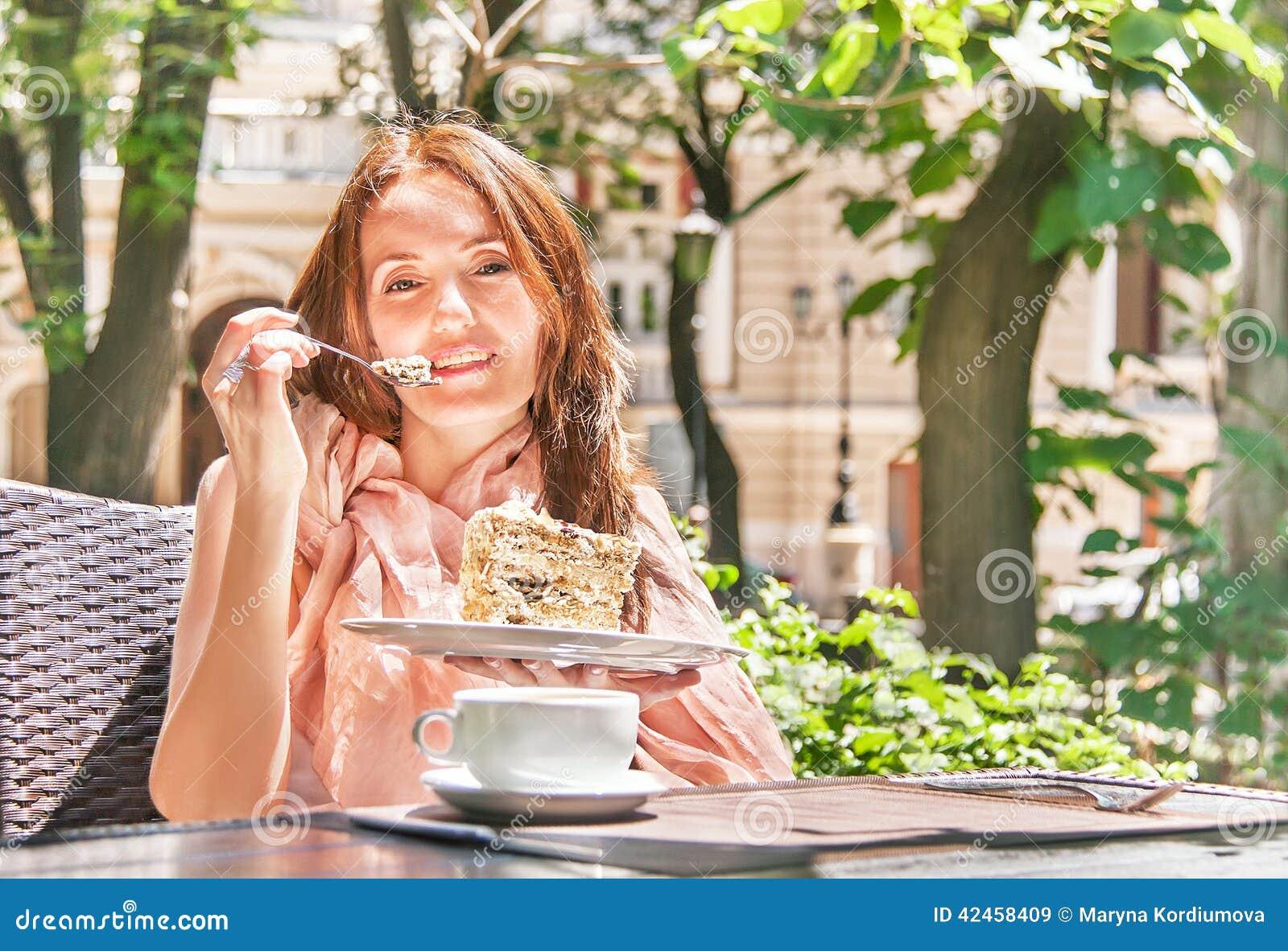 Mädchen isst einen Nachtisch (Kuchen) im café