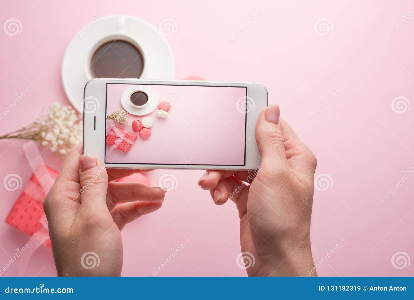 Mädchen macht Fotos an einem Telefon auf einem rosa Hintergrund des Kaffees und der Makronen, für ein instagram