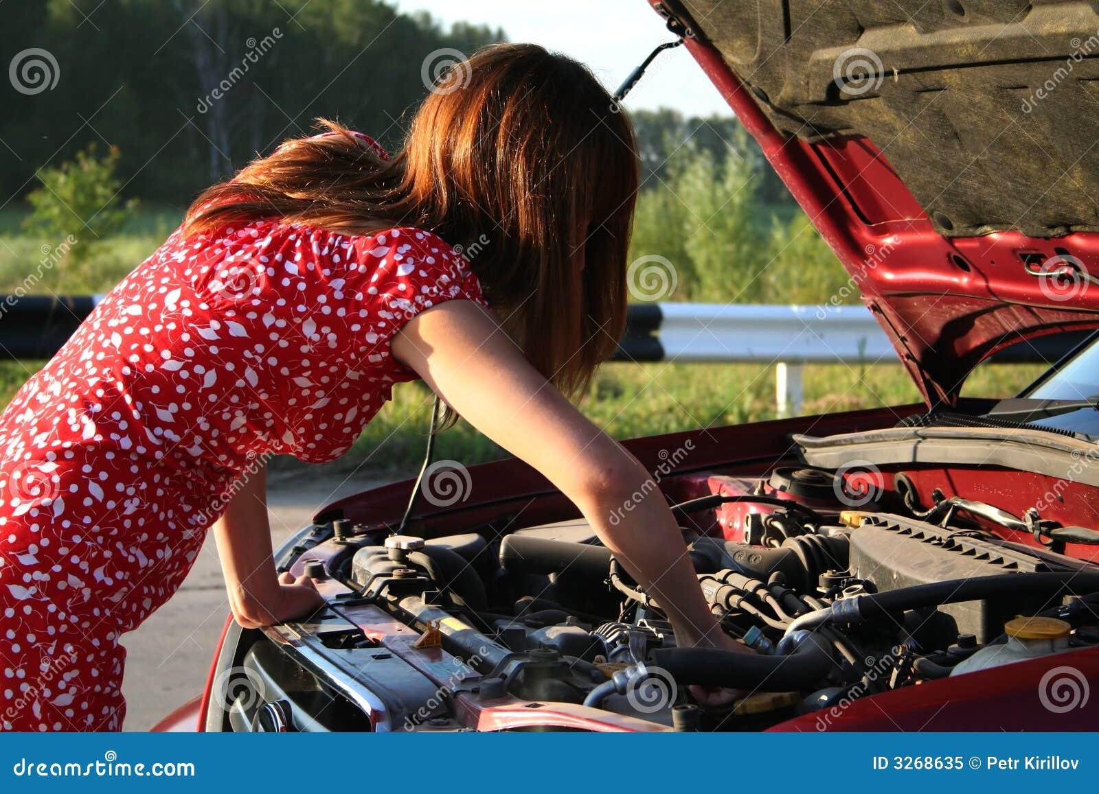 Junges mädchen welches das auto repariert