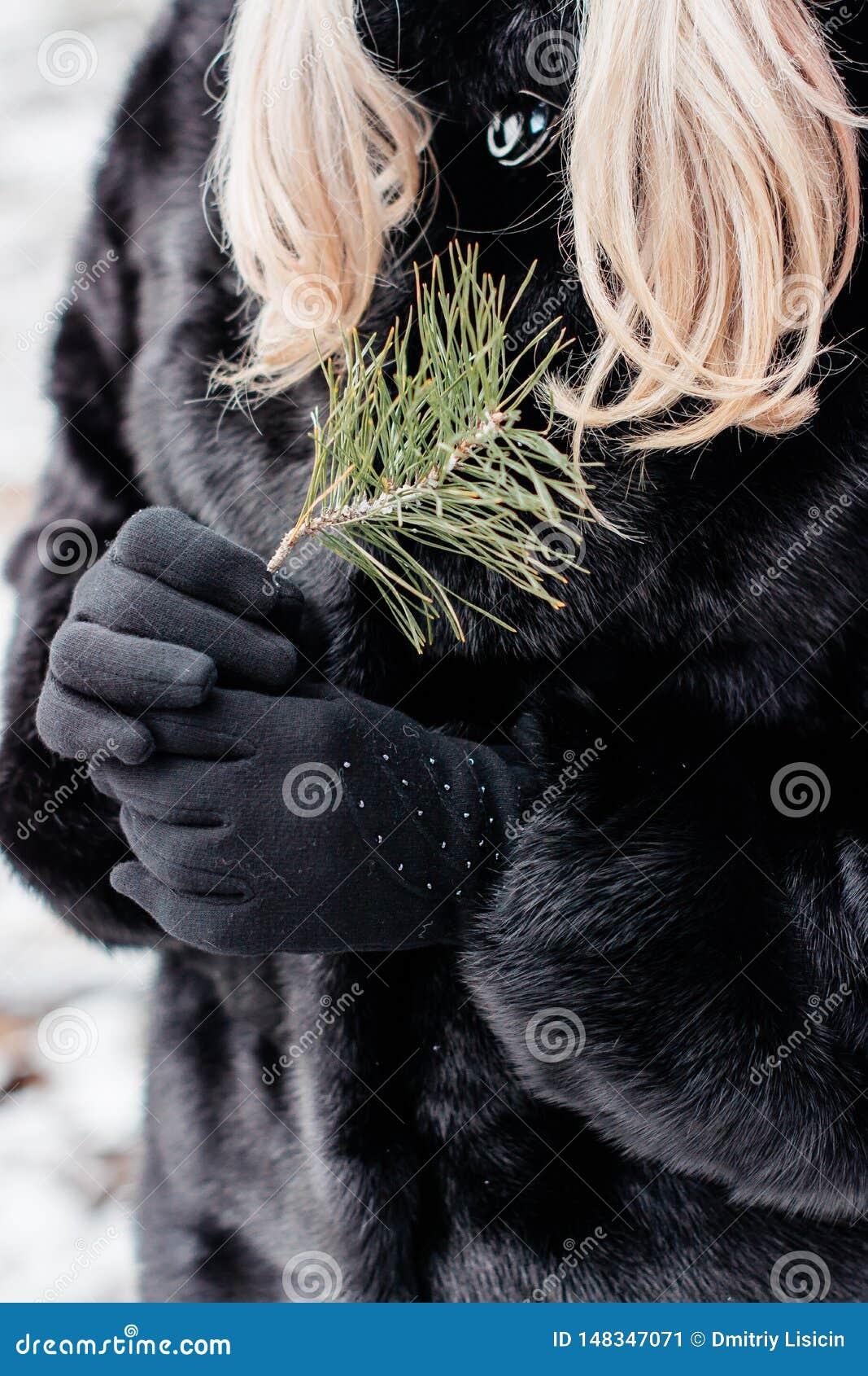 M?dchen mit dem blonden Haar und schwarzem Mantel