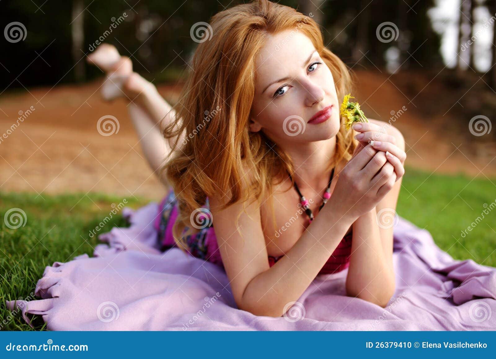 Mädchen mit dem roten Haar auf grünem Gras