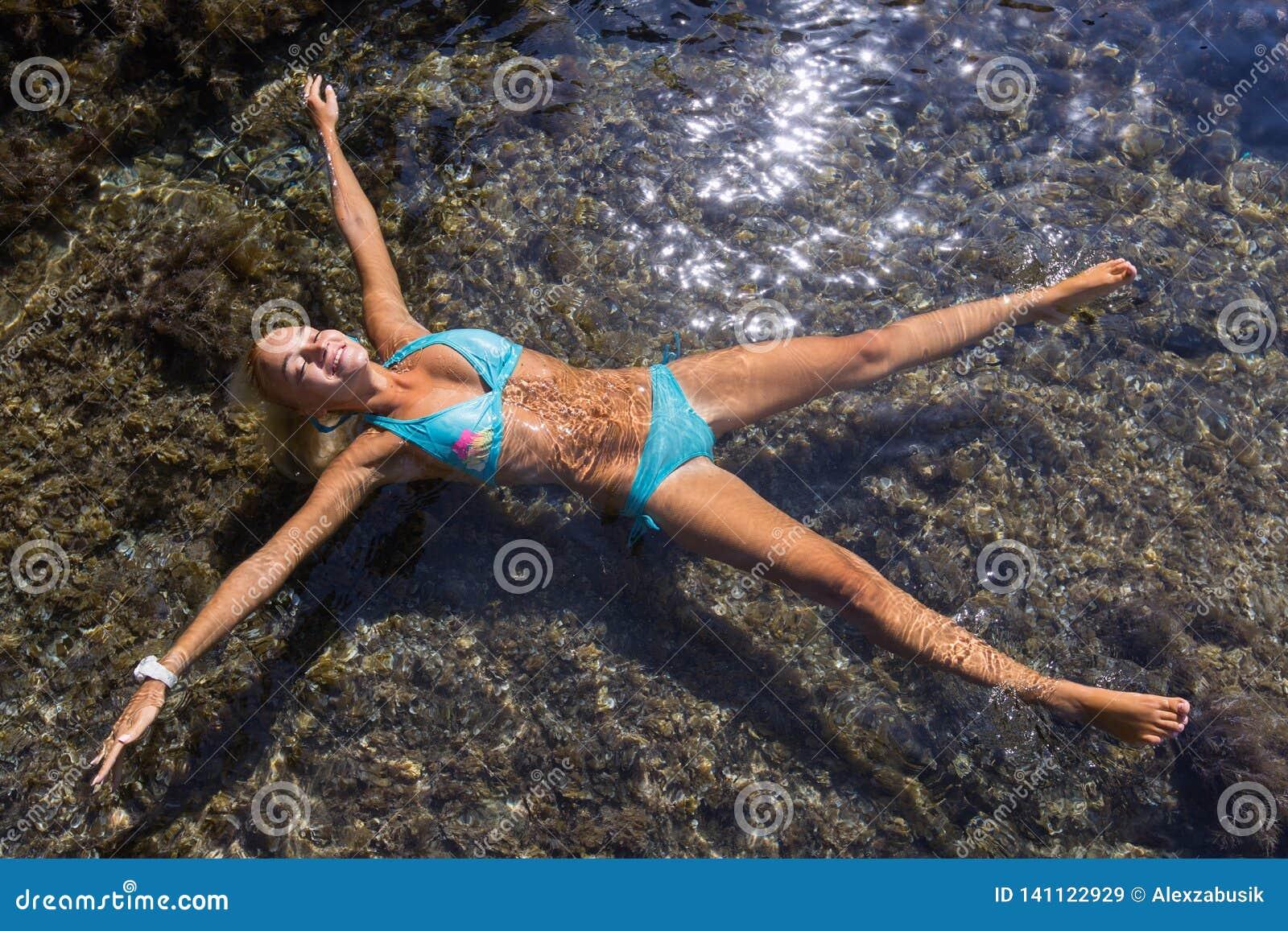Mädchen mit den ausgestreckten Armen und den Beinen liegt auseinander auf Wasser