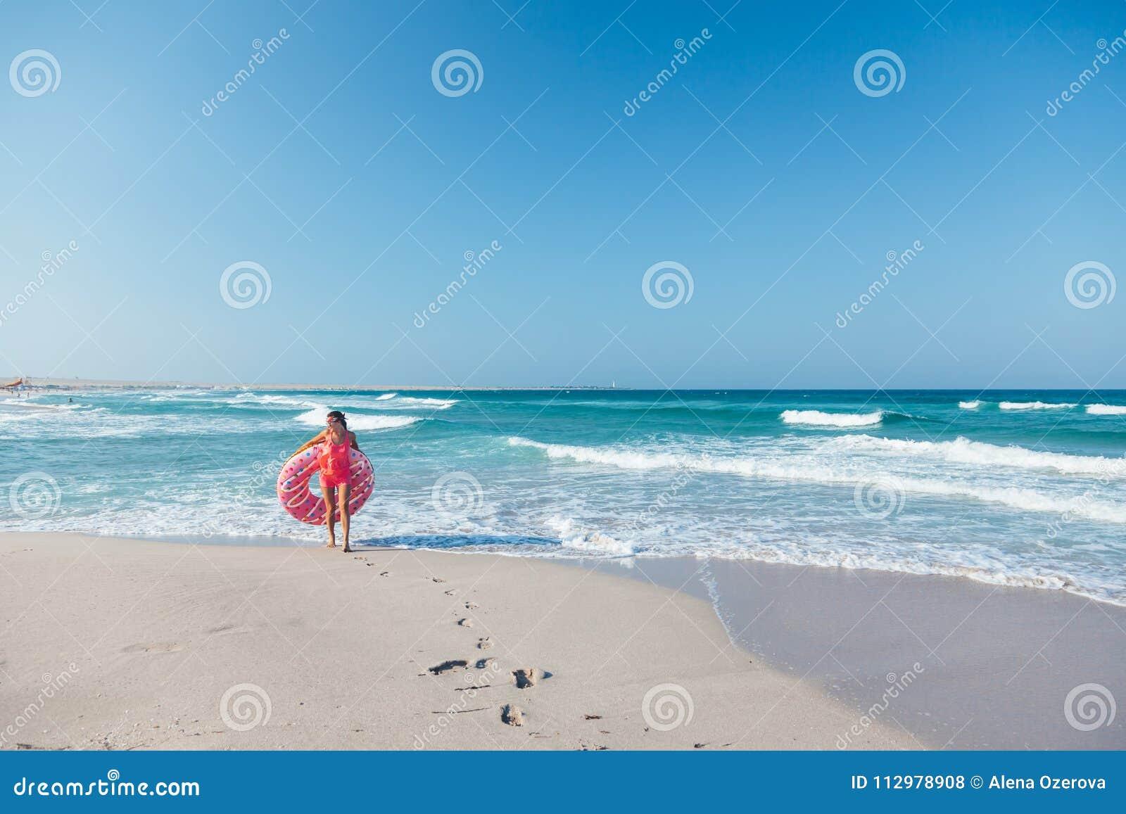 Mädchen mit Donut lilo auf dem Strand
