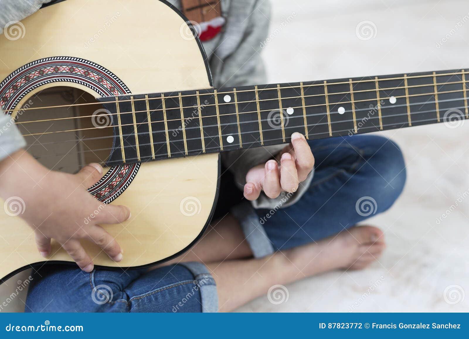 Mädchen mit 9-Jährigen, das lernt, die Gitarre zu spielen