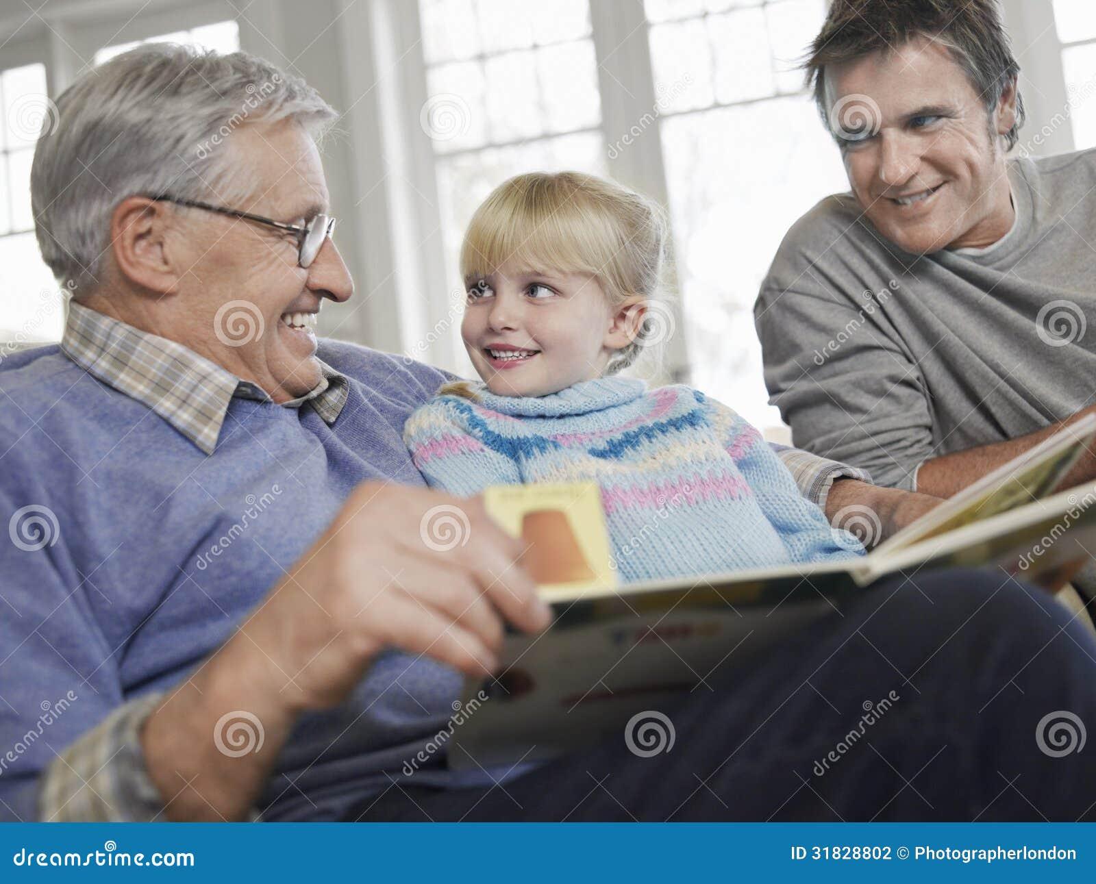 Mädchen mit Vater-And Grandfather Reading-Geschichten-Buch