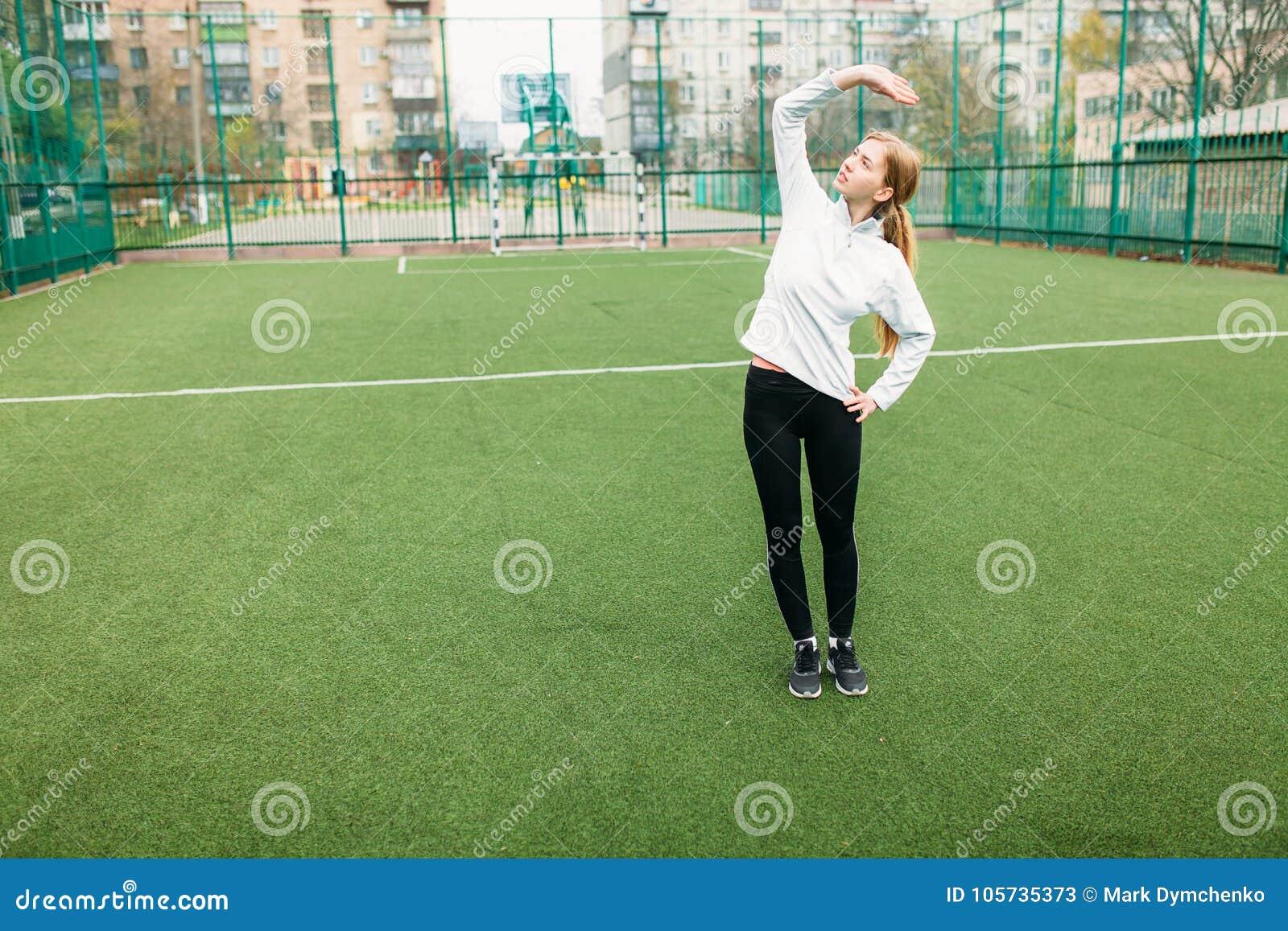 Mädchen nach der Ausbildung, dem Laufen oder Sport ein Rest im Vordergrund, eine Flasche Wasser Das Mädchen arbeitet in der offen