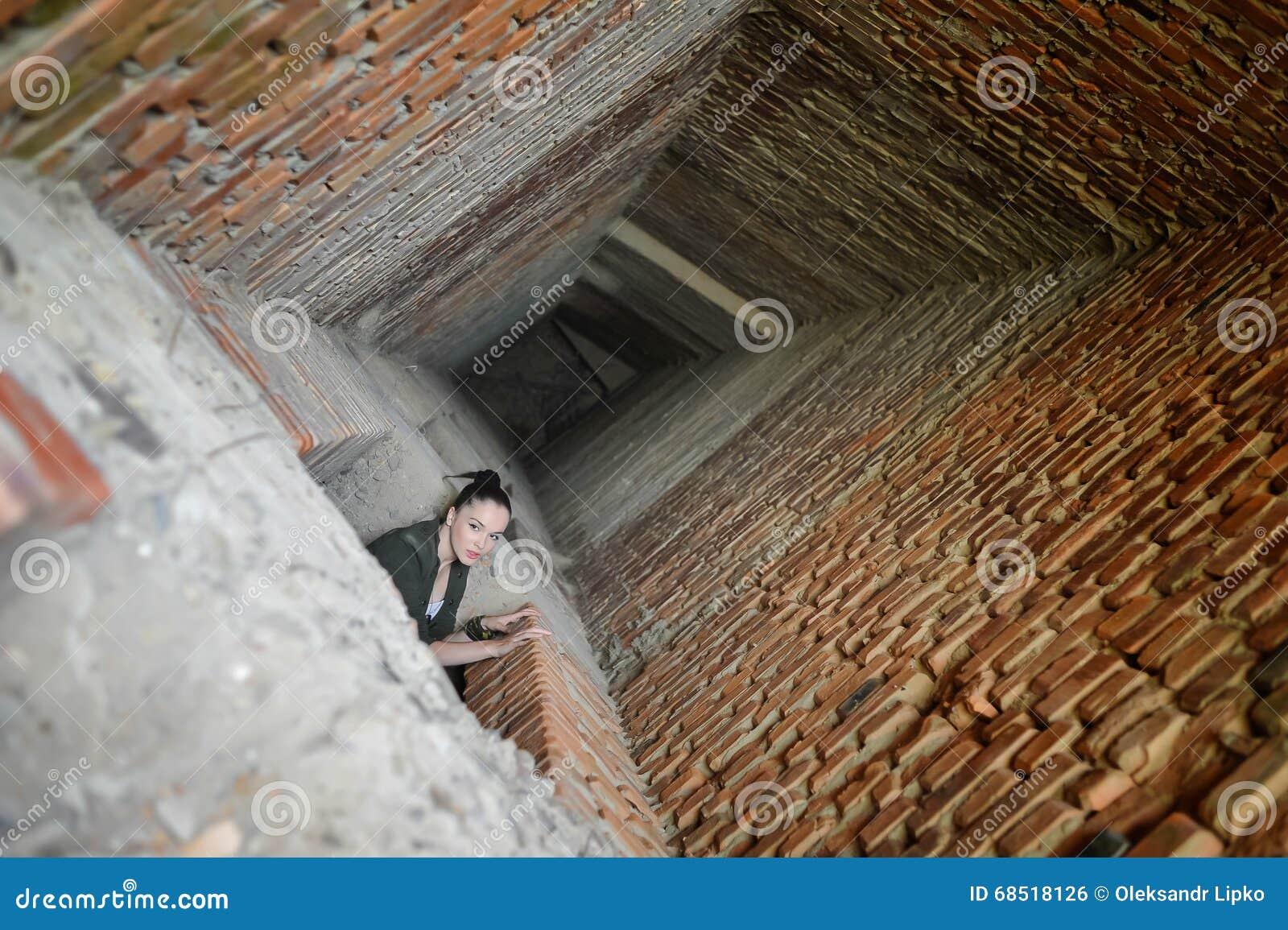 Mädchen nahe der Backsteinmauer in der Militärart