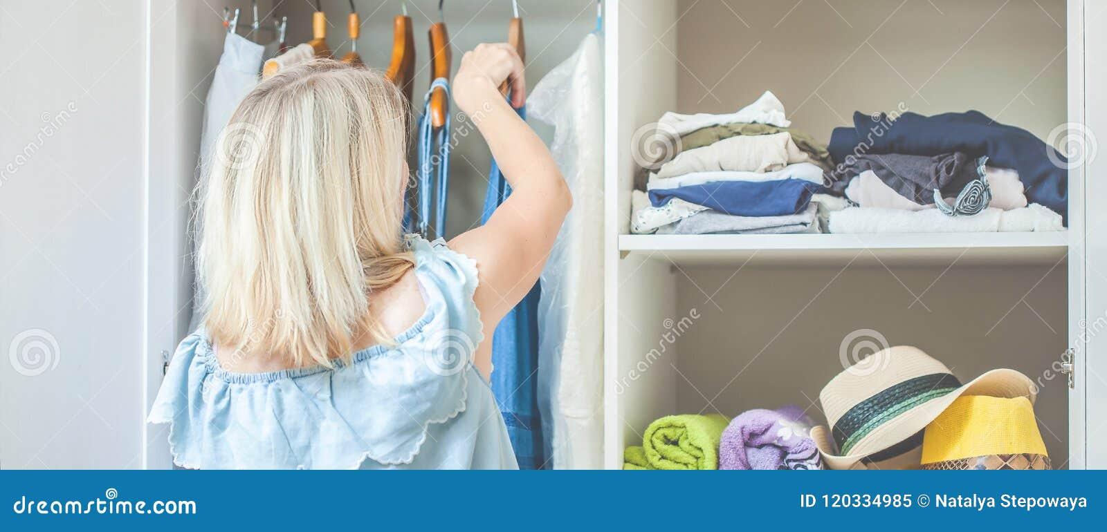 Mädchen nahe einer Garderobe mit Kleidung kann was nicht wählen zu tragen Schweres auserlesenes Konzept hat nichts, Fahne zu trag