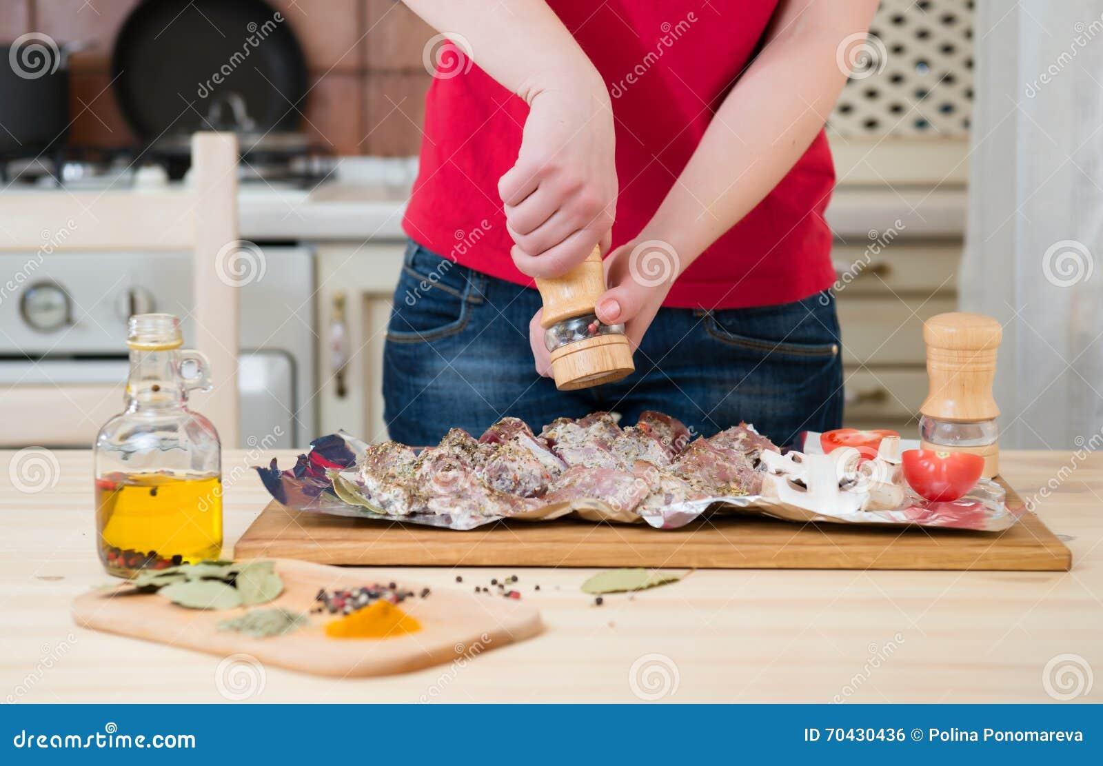 Mädchen pfeffert Fleisch auf Gewürzen und Gemüse einer Tabelle Zwei zusammenhaltene Hände