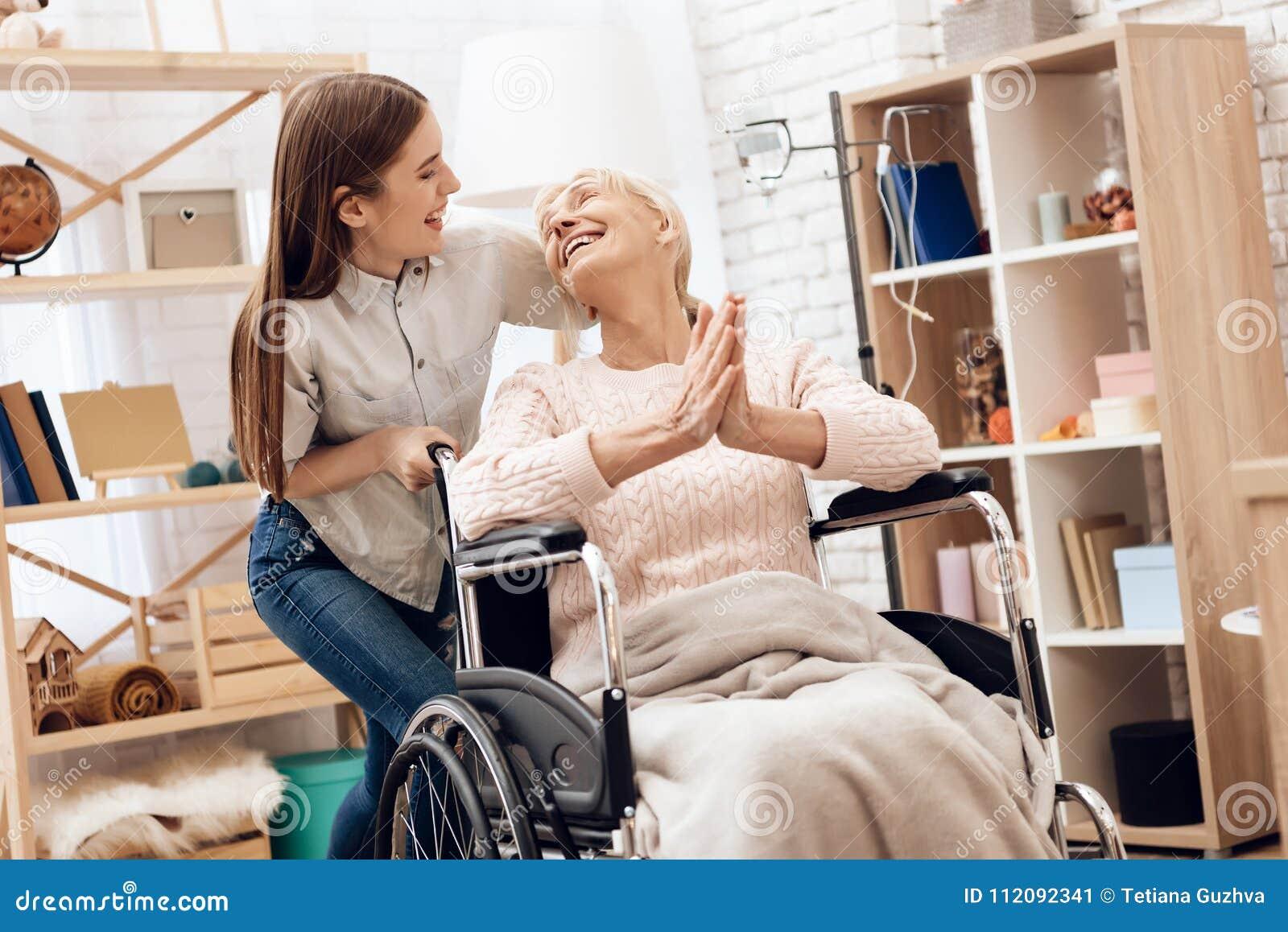 Mädchen pflegt ältere Frau zu Hause Mädchen reitet Frau im Rollstuhl Frau amüsiert sich