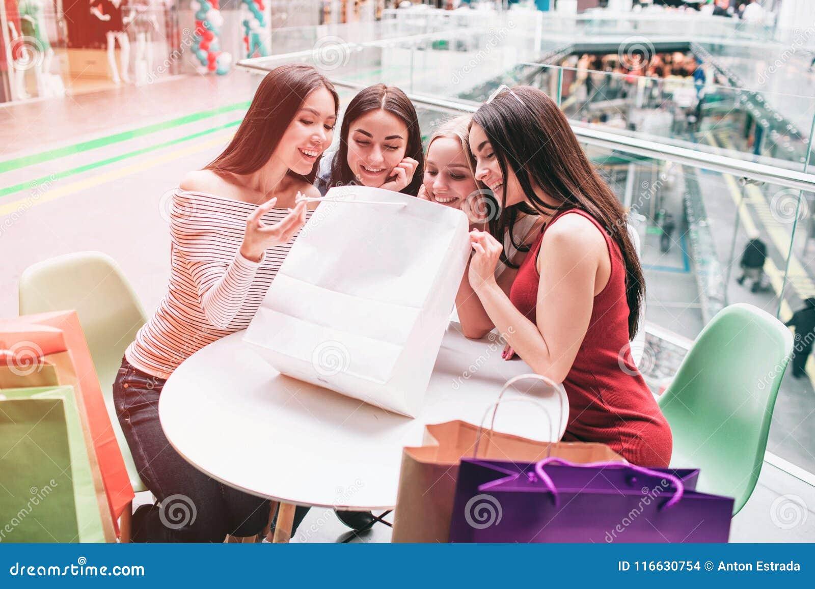 Mädchen sitzen am Tisch und untersuchen Einkaufstasche Sie sind glücklich und sehr aufgeregt