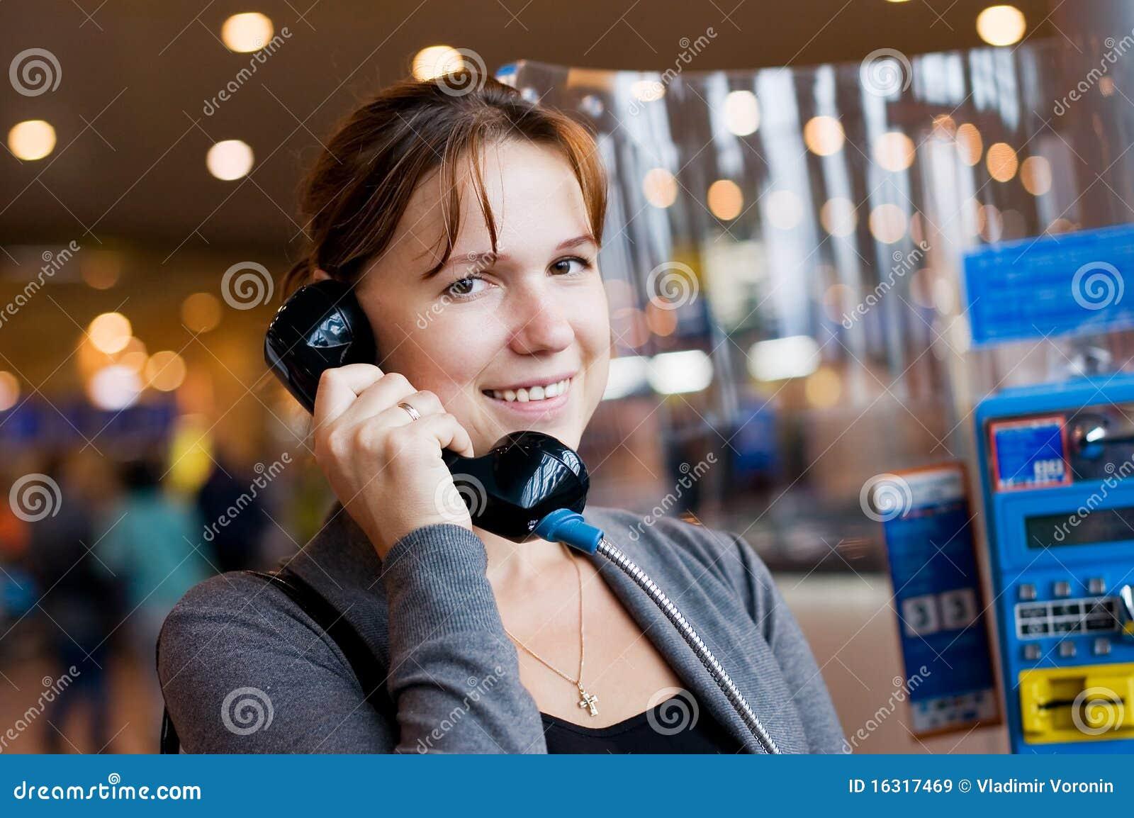 Mädchen spricht durch Telefon am Flughafen