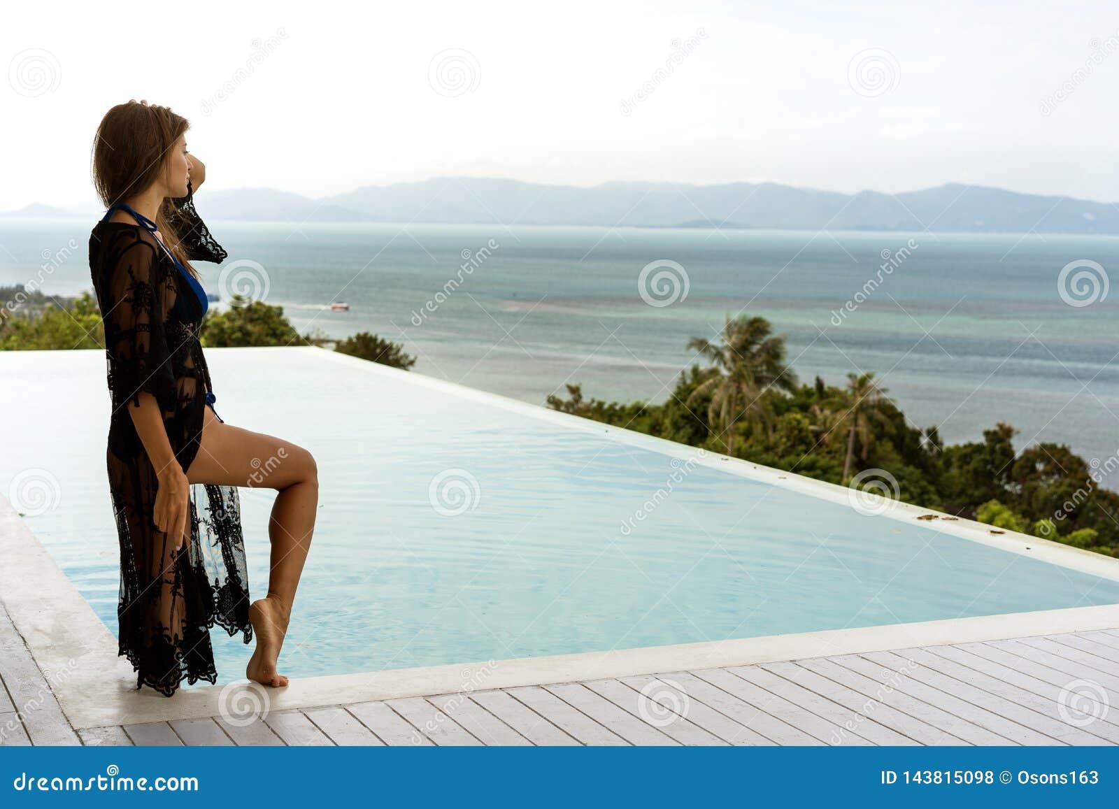 Mädchen steht auf der Küste, welche die Berge nahe dem Pool übersieht