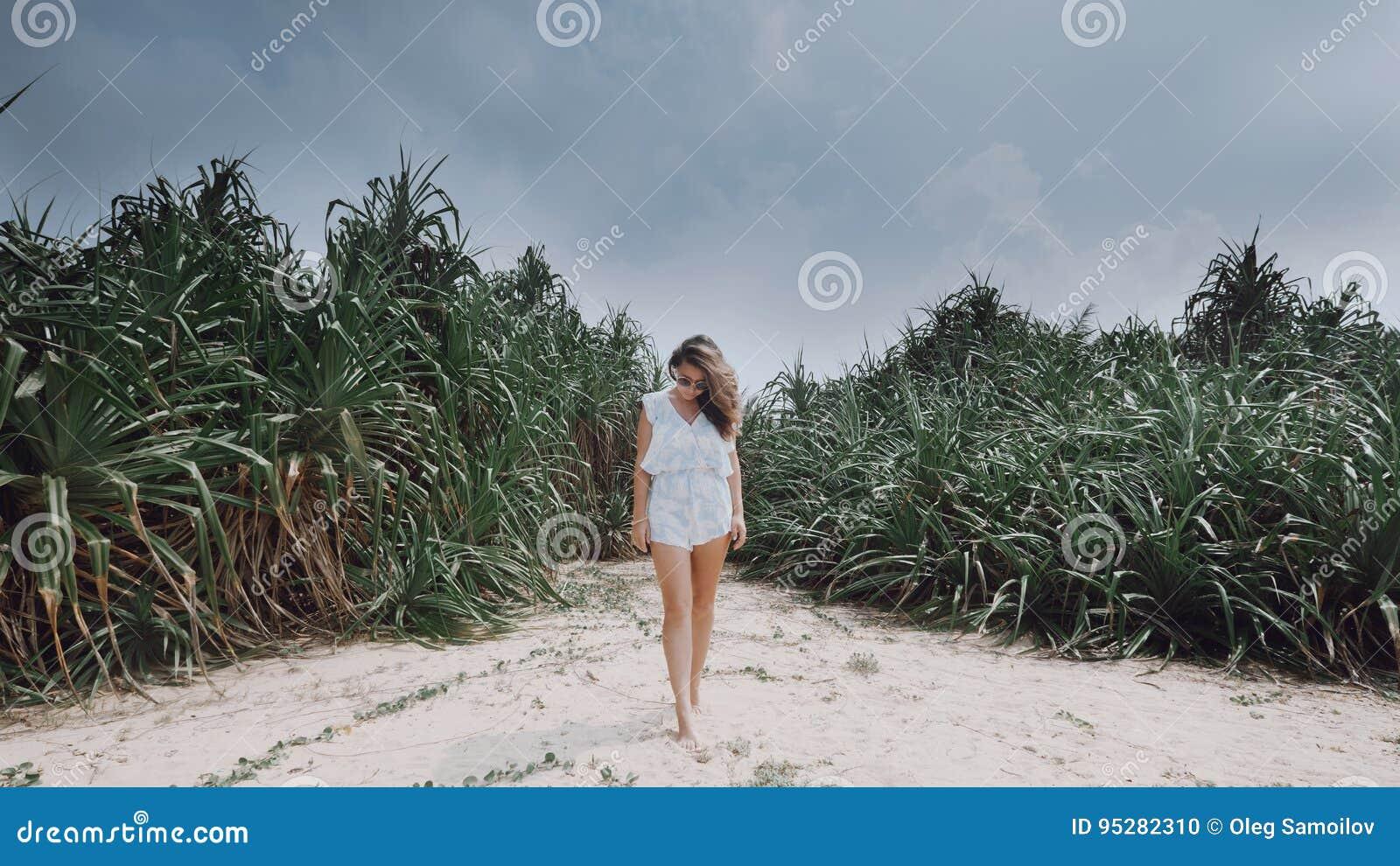 Mädchen steht vor dem hintergrund der exotischen Anlagen auf dem Strand